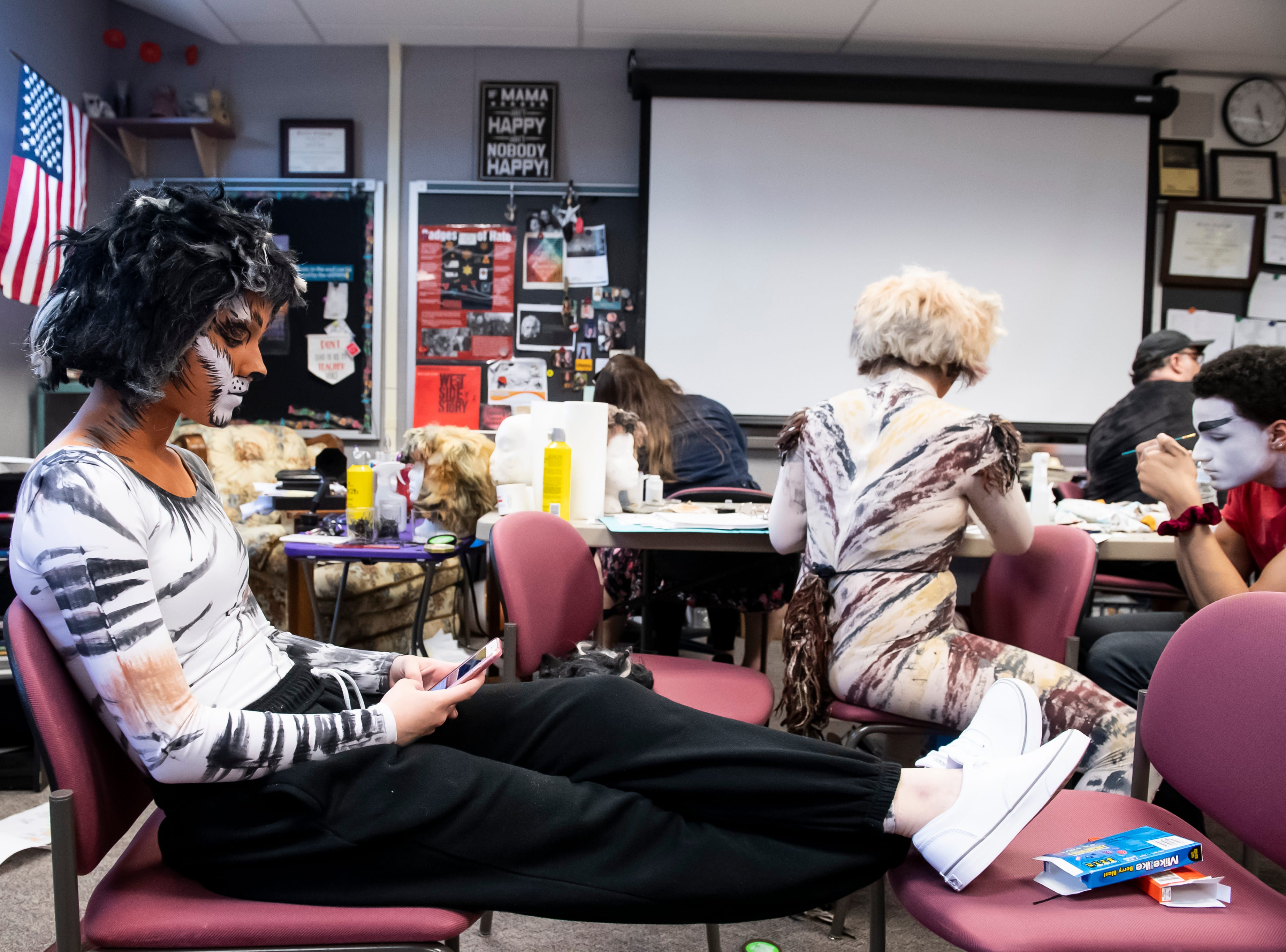 """Erin Homan checks her phone before the start of a dress rehearsal for Hanover High School's production of """"Cats"""" on Wednesday, April 10, 2019."""