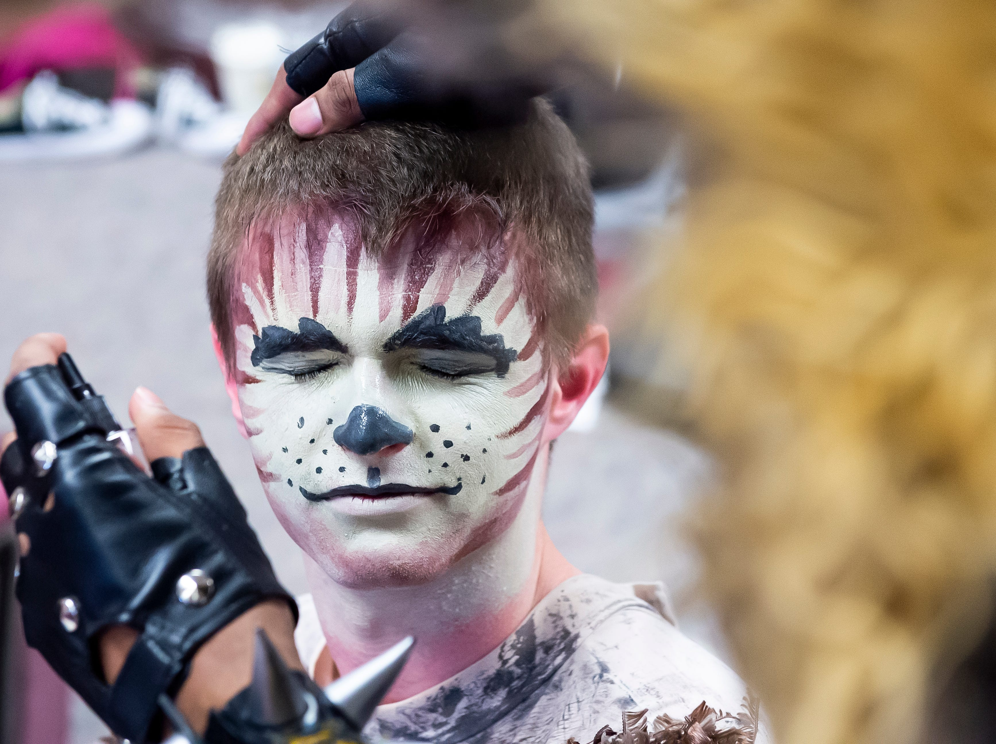 """Senior Matthew Hutton gets some makeup setting spray applied to his face before the start of a dress rehearsal for the Hanover High School production of """"Cats"""" on Wednesday, April 10, 2019."""