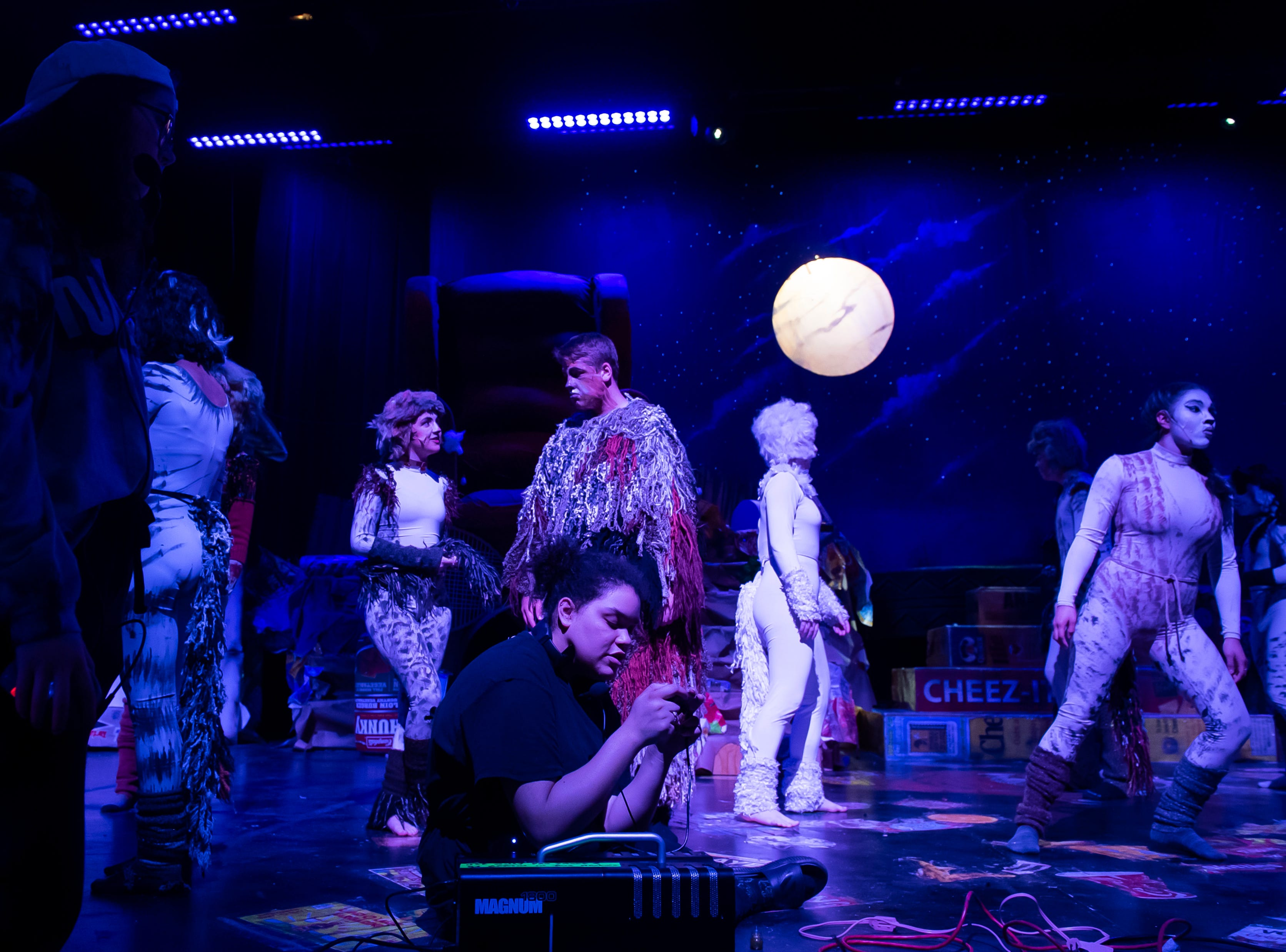 """Stage manager Alexus Faisal (bottom center) works on a fog machine as students prepare for the the start of a dress rehearsal at Hanover High School's production of """"Cats"""" on Wednesday, April 10, 2019."""