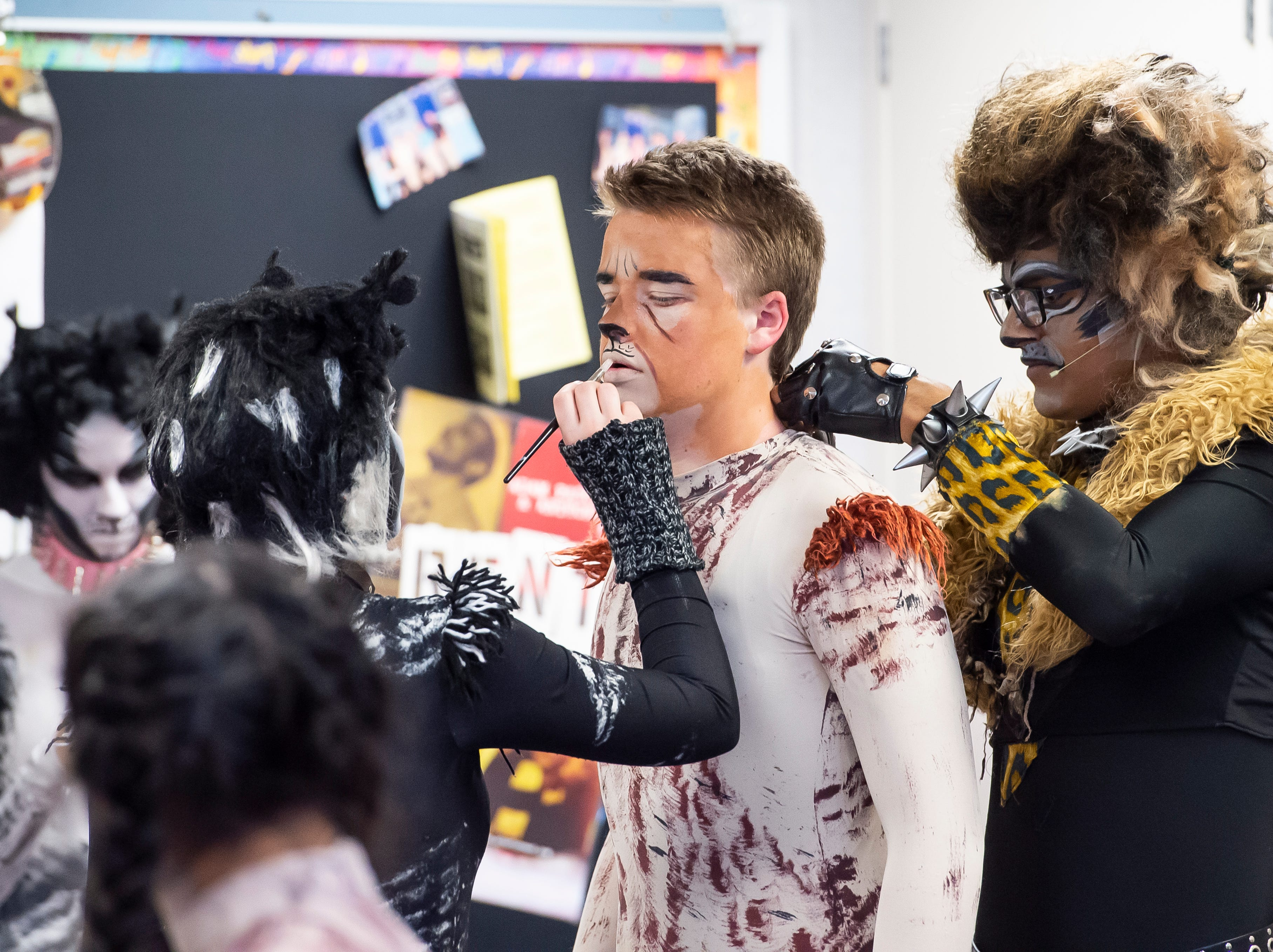 """Tyler Newman, center, gets some help with his makeup and costume before the start of a dress rehearsal for the Hanover High School production of """"Cats"""" on Wednesday, April 10, 2019."""
