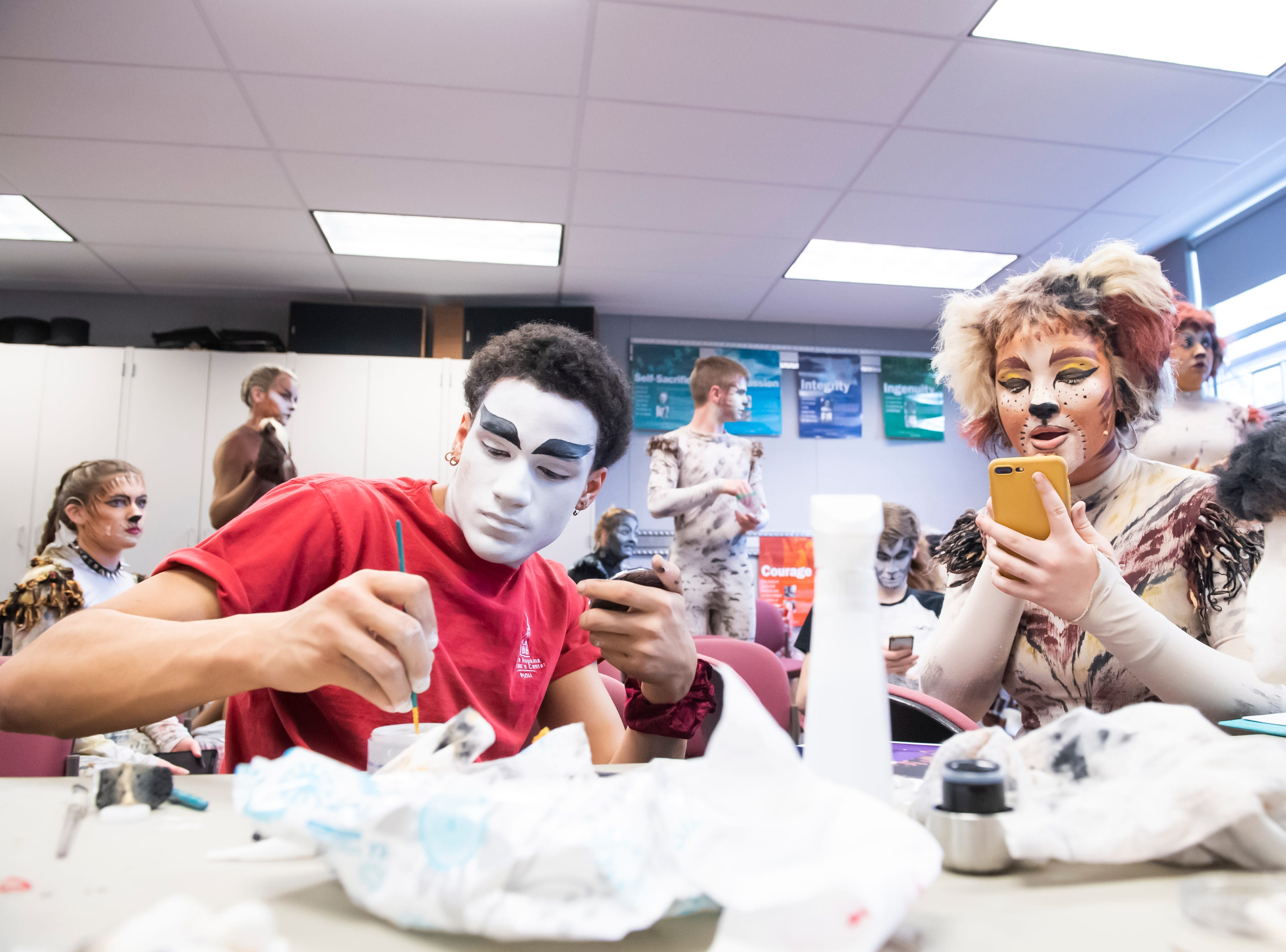 """Malcolm Ellis, left, and Aleana Williams apply makeup to themselves before the start of a dress rehearsal for Hanover High School's production of """"Cats"""" on Wednesday, April 10, 2019."""