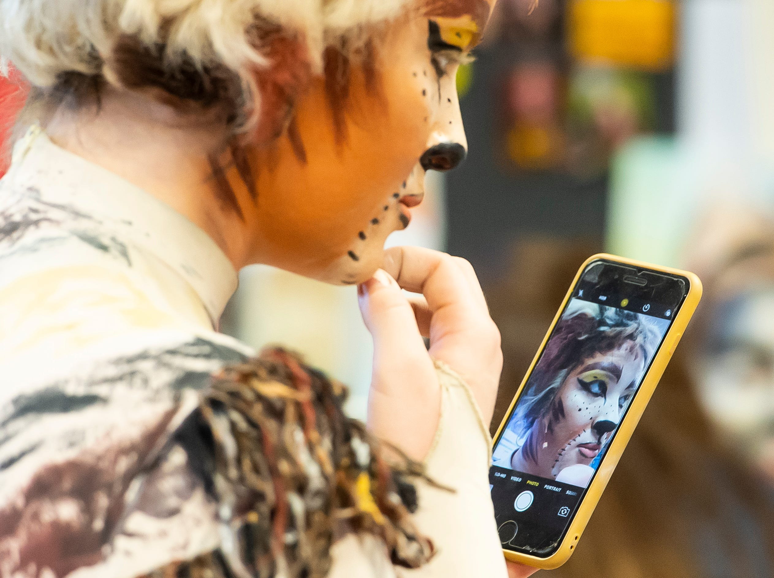 """Aleana Williams uses her phone to check her makeup before the start of a dress rehearsal for the Hanover High School production of """"Cats"""" on Wednesday, April 10, 2019."""