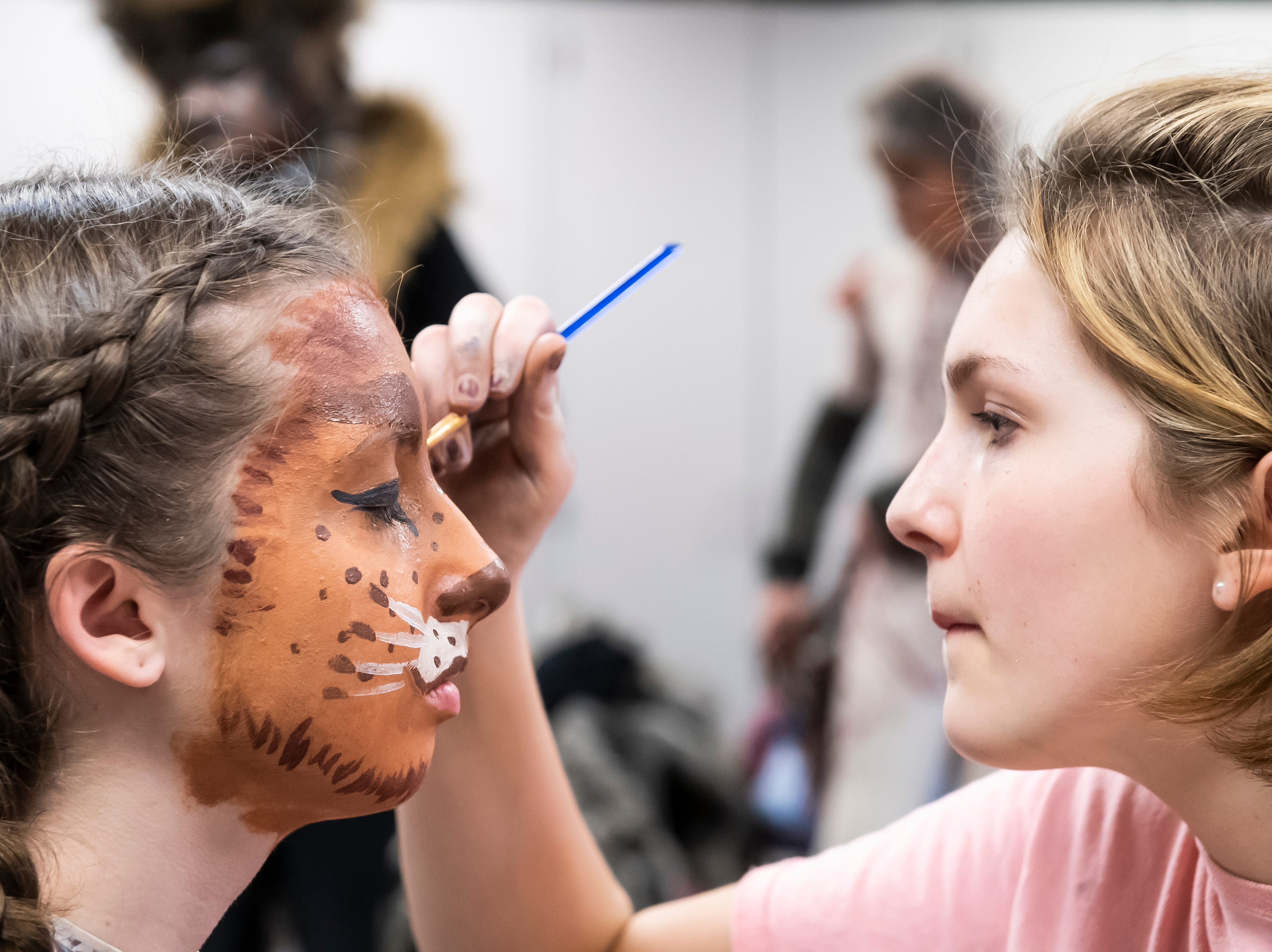 """Abby Duvall, right, works on Emily Crouse's face makeup at  a dress rehearsal for Hanover High School's production of """"Cats"""" on Wednesday, April 10, 2019."""
