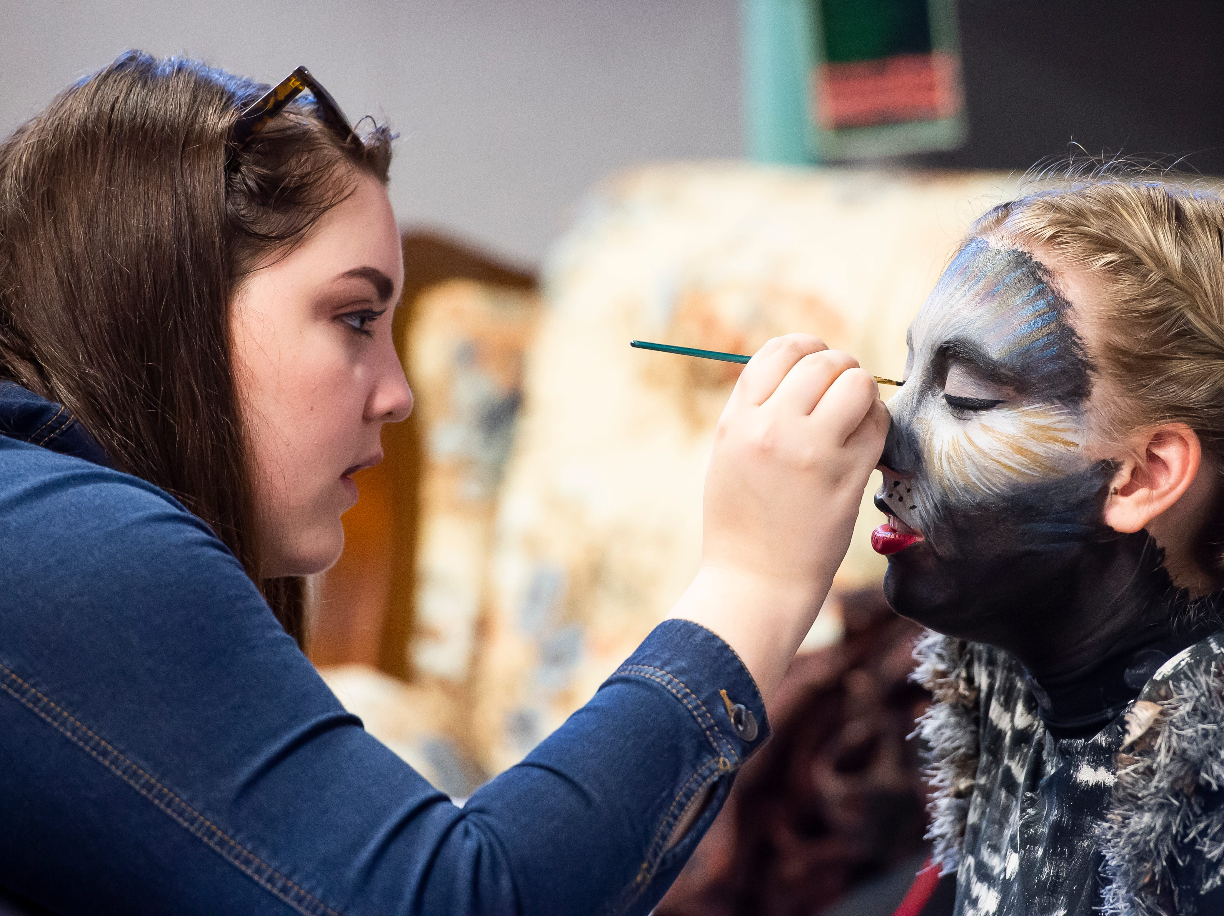"""Pressley McMaster works on Regin Smith's face makeup before the start of a dress rehearsal for the Hanover High School production of """"Cats"""" on Wednesday, April 10, 2019."""