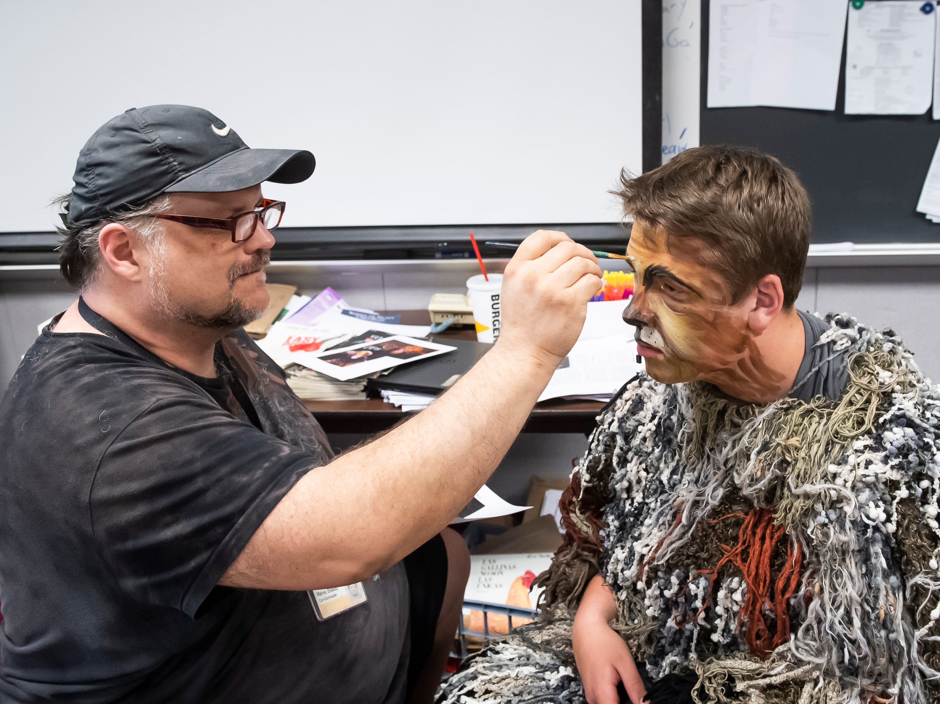 """Director Rene Staub applies makeup to Ben Newman's face before the start of a dress rehearsal for Hanover High School's production of """"Cats"""" on Wednesday, April 10, 2019. Newman plays the role of principle character Old Deuteronomy."""