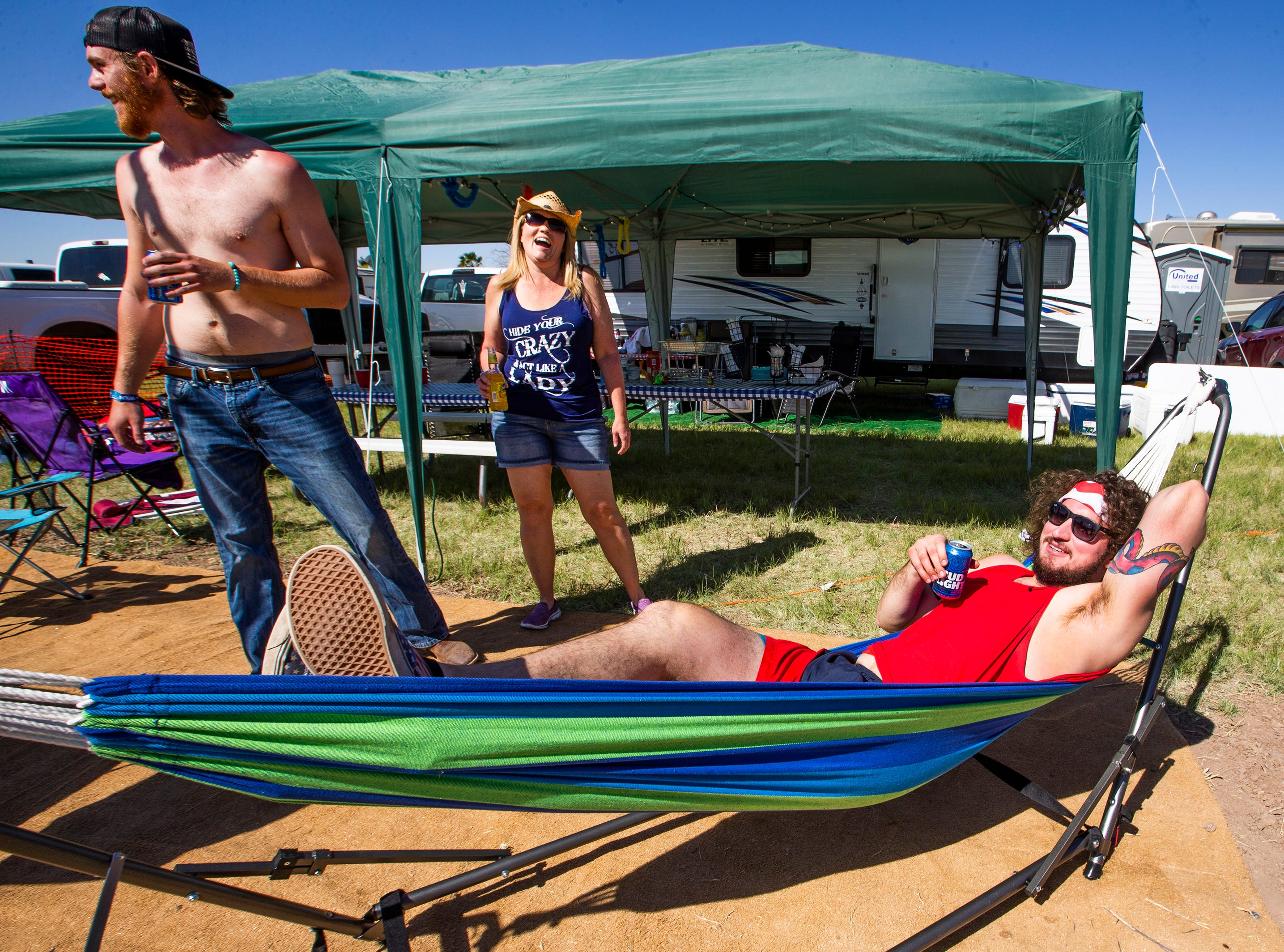 Jacob Callaway, 21, of Phoenix, enjoys a breakfast beer in his hammock after waking up in his camp at the Country Thunder Arizona 2019 music festival April 11, 2019.