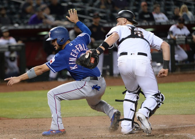 Apr 10, 2019; Phoenix, AZ, USA; Texas Rangers catcher Isiah Kiner-Falefa (9) slides at home ahead of the tag by Arizona Diamondbacks catcher Carson Kelly (18) during the ninth inning at Chase Field. Mandatory Credit: Joe Camporeale-USA TODAY Sports