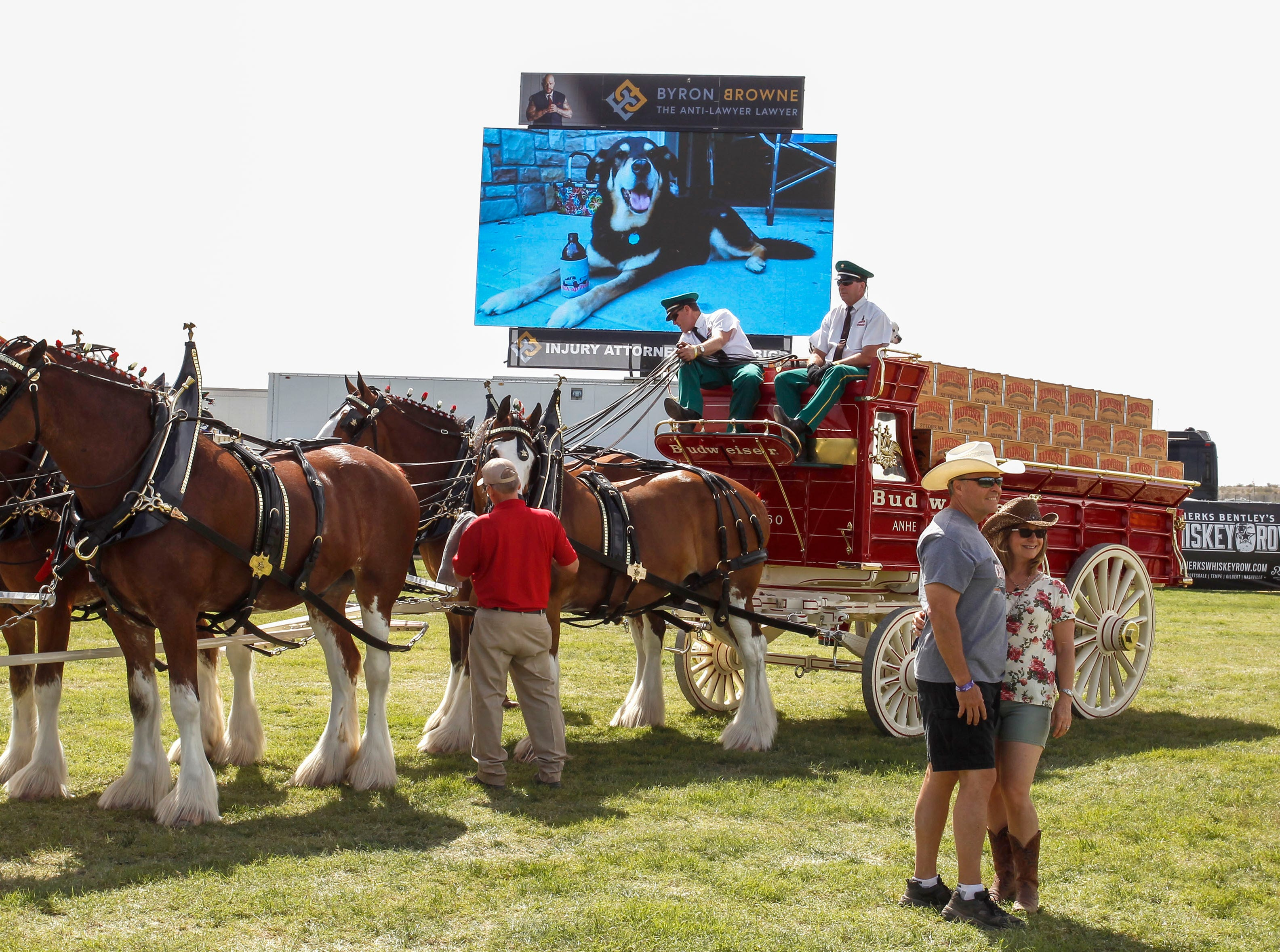 Country Thunder music goers pose in front of the Budweiser Clydesdales during Country Thunder Arizona on April 11, 2019, in Florence.
