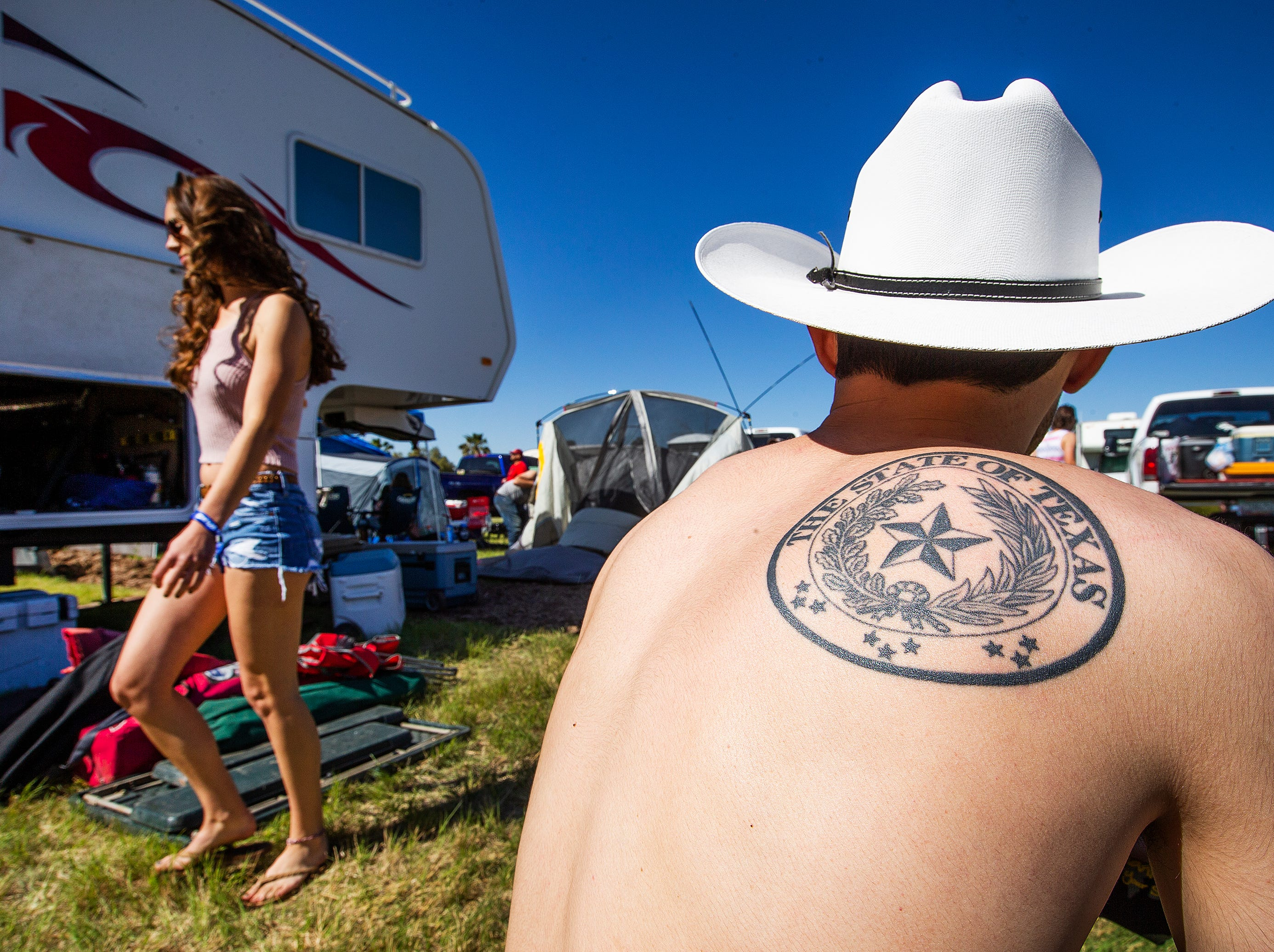 Texas native Cameron Glass, 23, of Chandler, proudly wears his Texas tattoo after waking up in his camp at the Country Thunder Arizona 2019 music festival April 11, 2019.