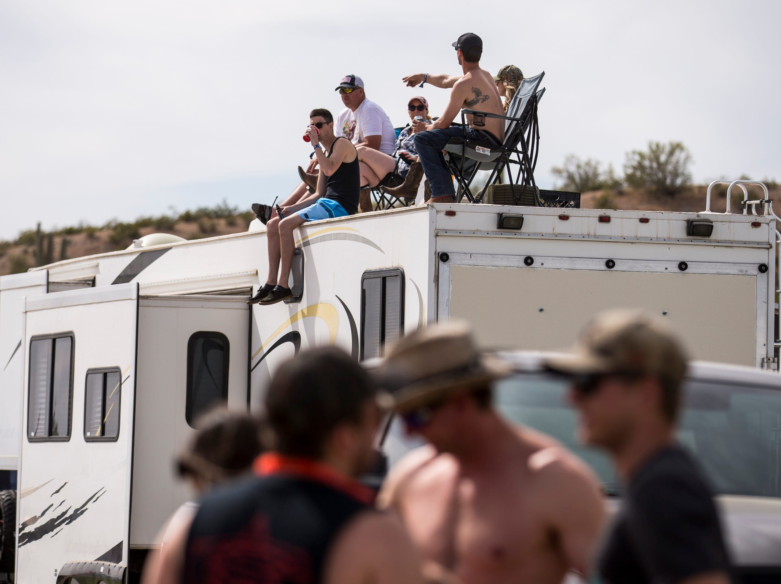 Festival-goers sit on top of an RV at the Crazy Coyote campsite on April 11, 2019, during Day 1 of Country Thunder Arizona in Florence.