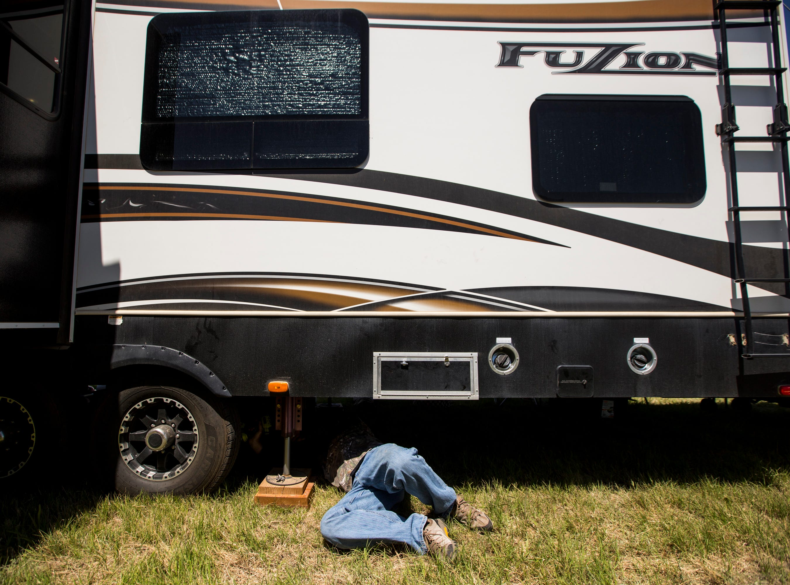 Kevin Blake works on an RV's electrical and drainage systems on April 11, 2019, during Day 1 of Country Thunder Arizona in Florence.