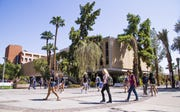 Arizona State University students walk past the Engineering G Building between classes on  the Tempe campus on Sept. 11, 2017.
