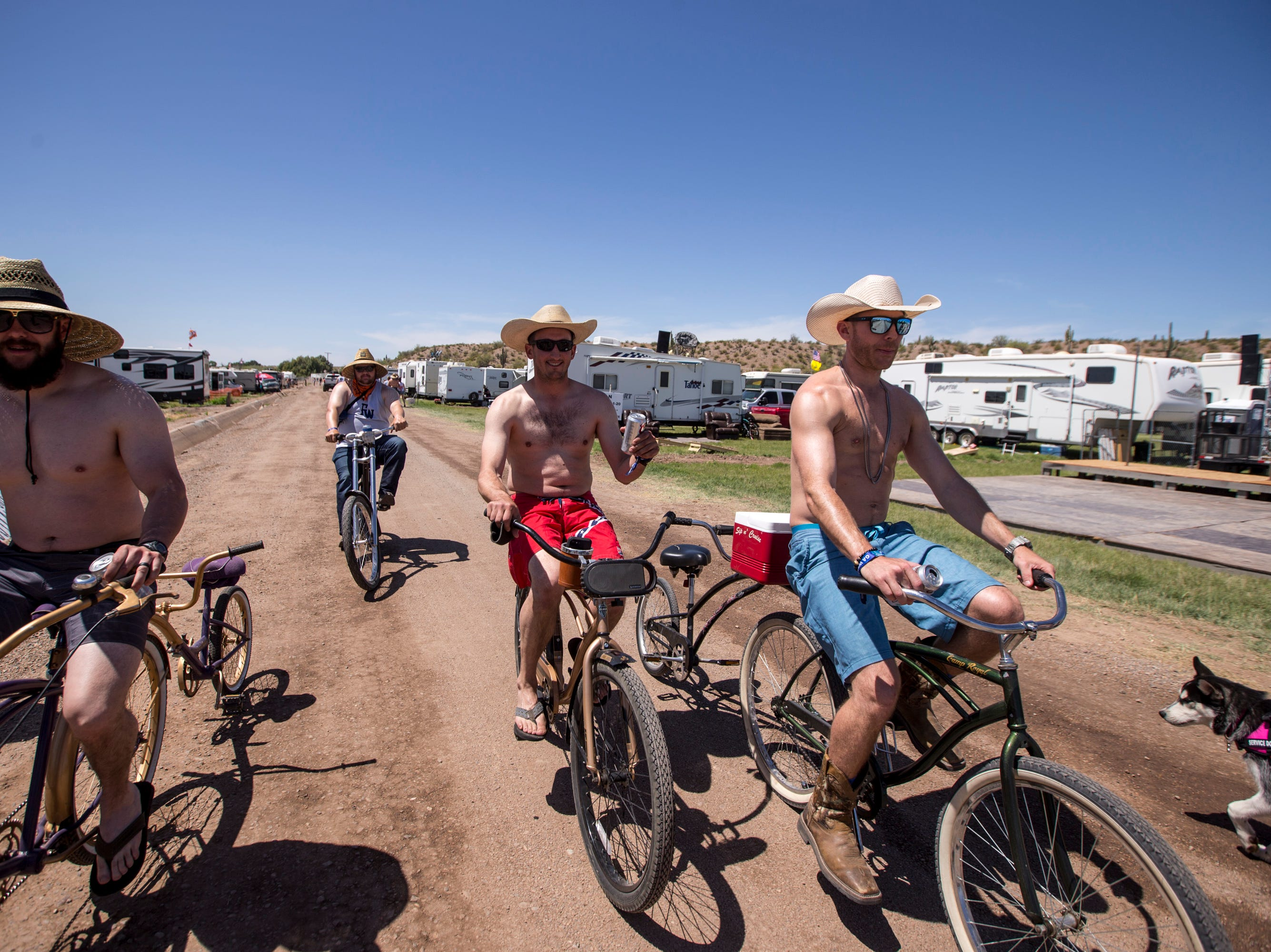 Festival-goers ride bikes around campsites on April 11, 2019, during Day 1 of Country Thunder Arizona in Florence.