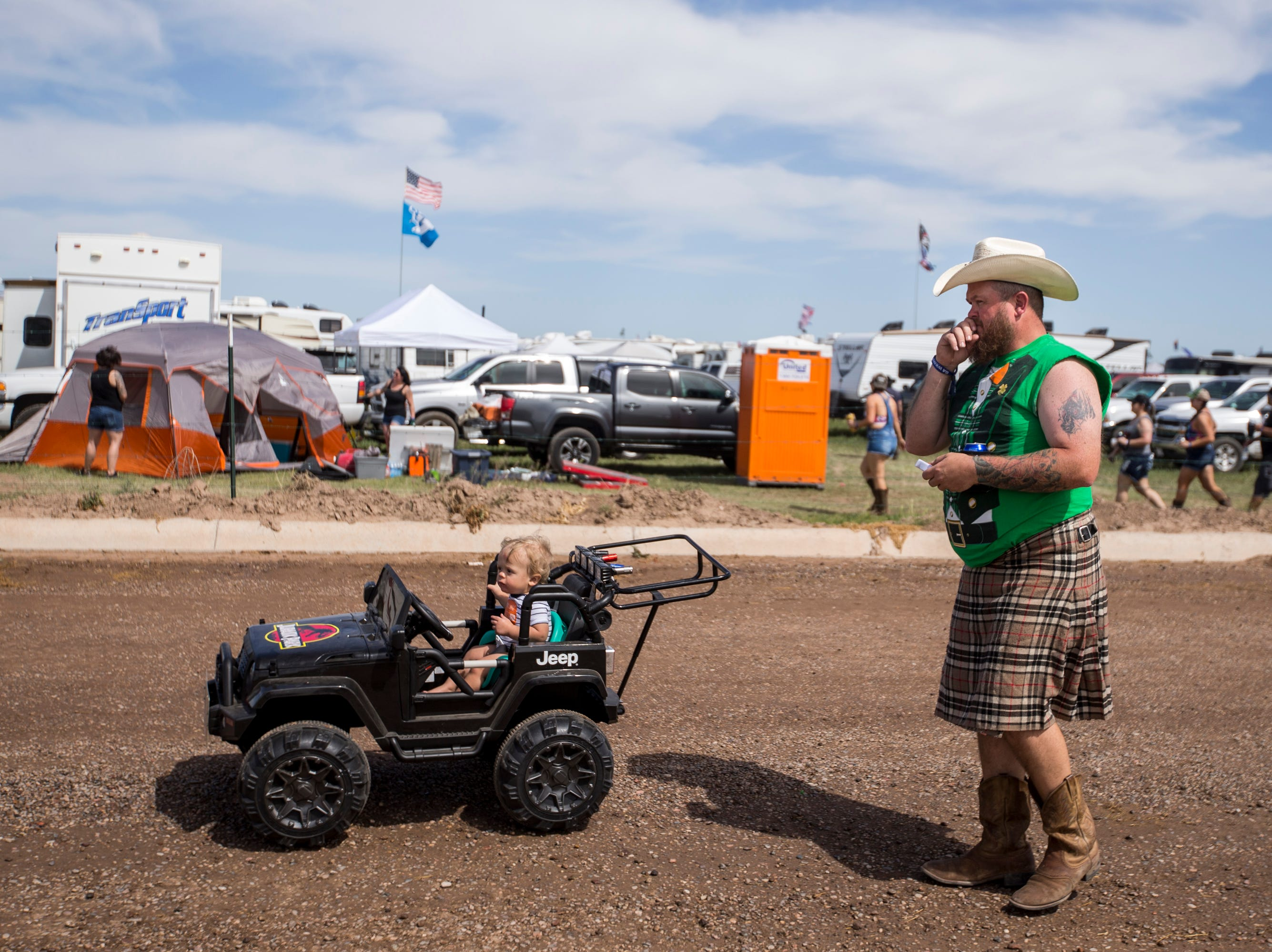 Sean Dwyer drives a motorized toy car with his son, Malakai, on April 11, 2019, during Day 1 of Country Thunder Arizona in Florence.
