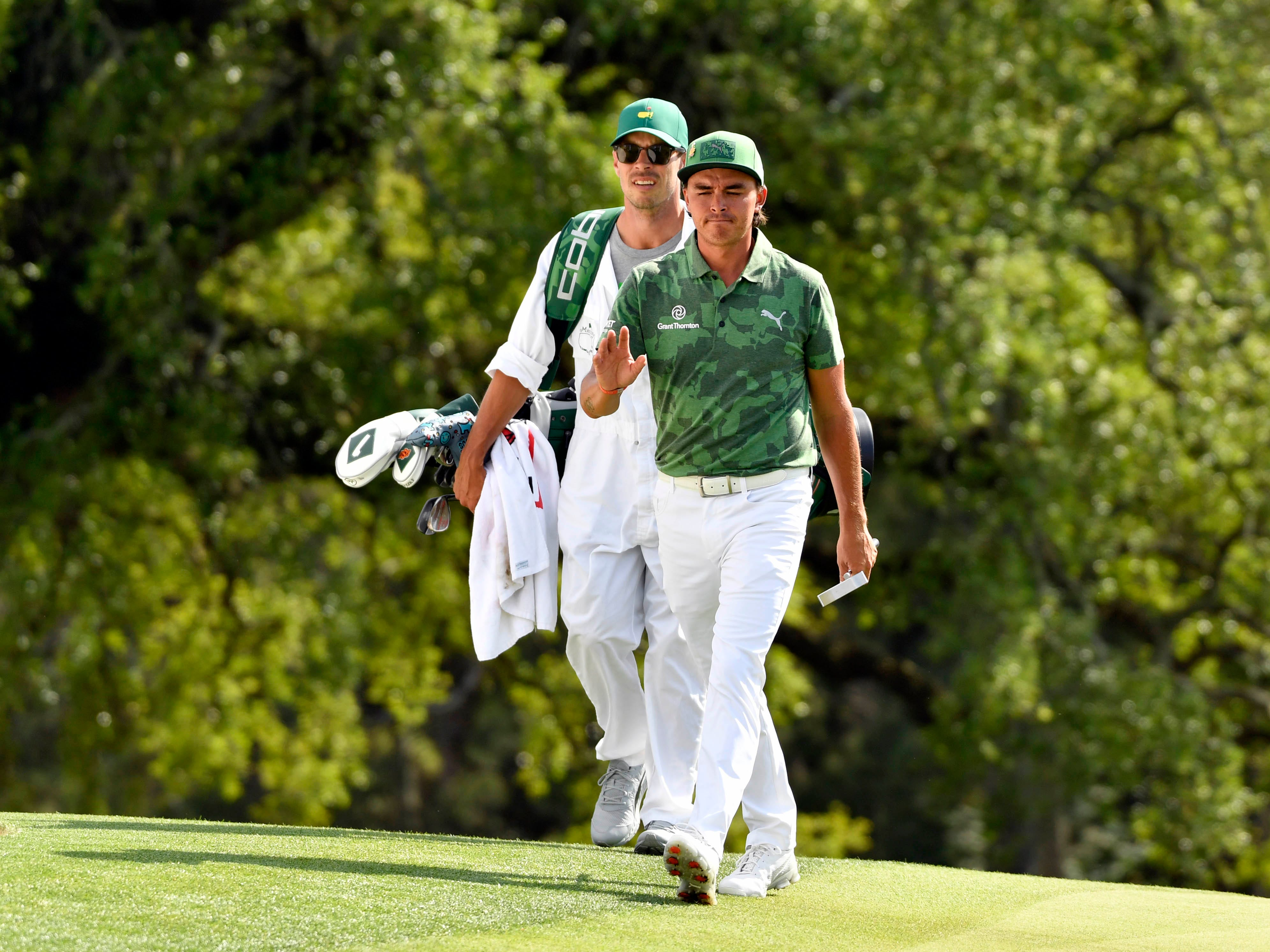 Apr 11, 2019; Augusta, GA, USA; Rickie Fowler and caddie Joseph Skovron to the 18th green during the first round of The Masters golf tournament at Augusta National Golf Club.