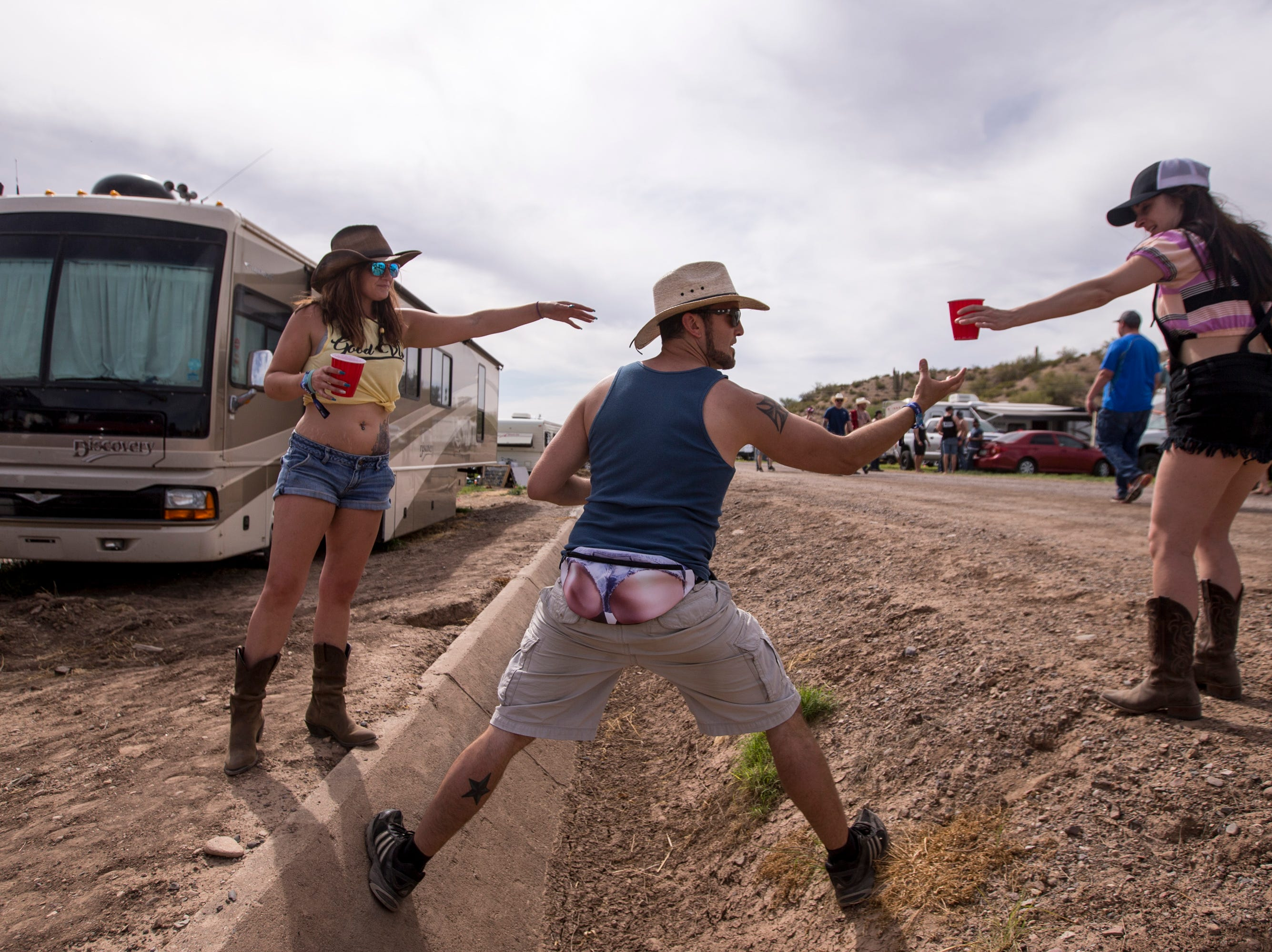 Tawni Williamson (left) watches as Andrew WK Hefley helps Brooke Humphrey cross a drainage ditch on April 11, 2019, during Day 1 of Country Thunder Arizona in Florence.