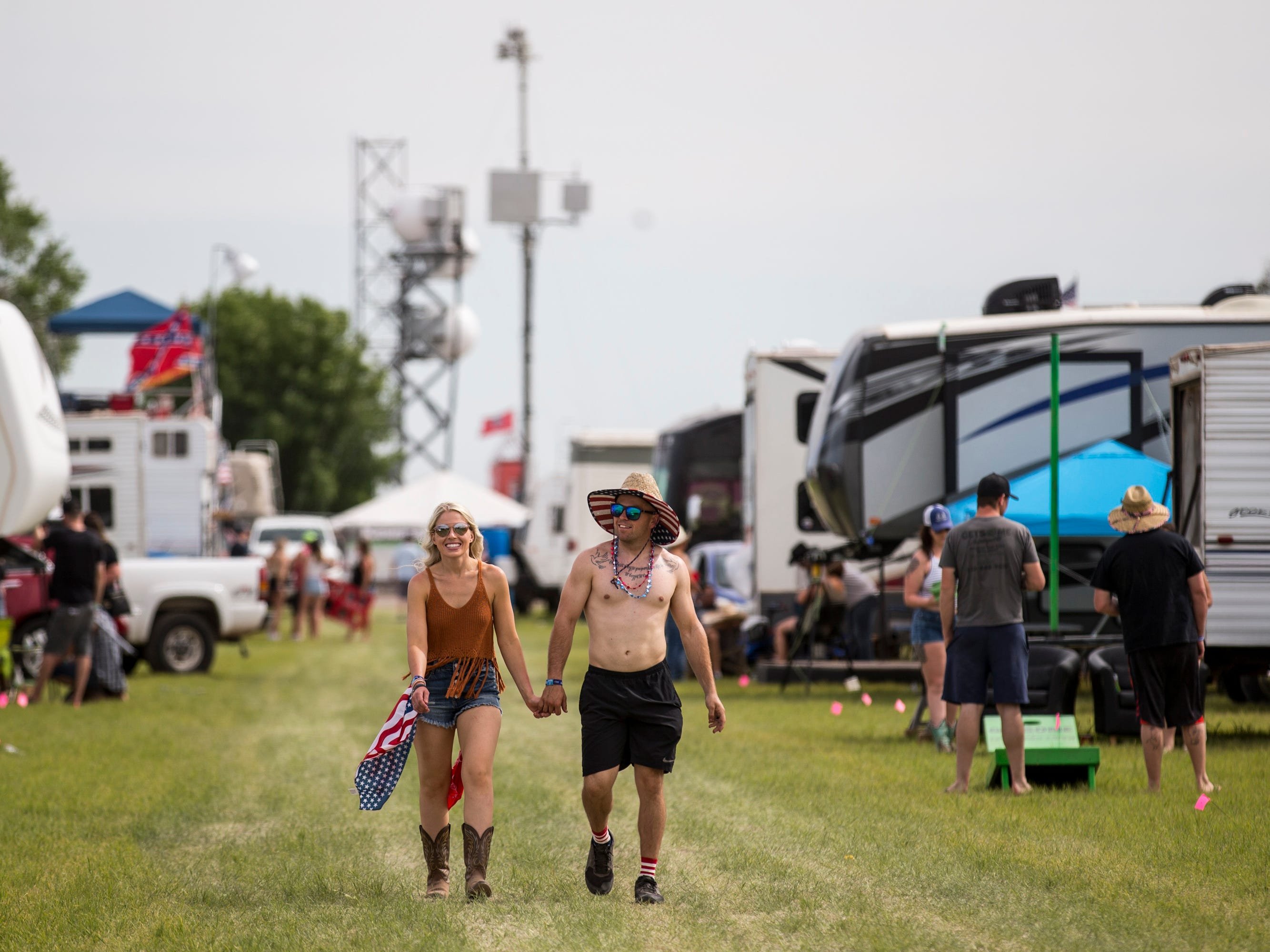 Kayla Walter and Ryan Walter walk through a campsite on April 11, 2019, during Day 1 of Country Thunder Arizona in Florence.