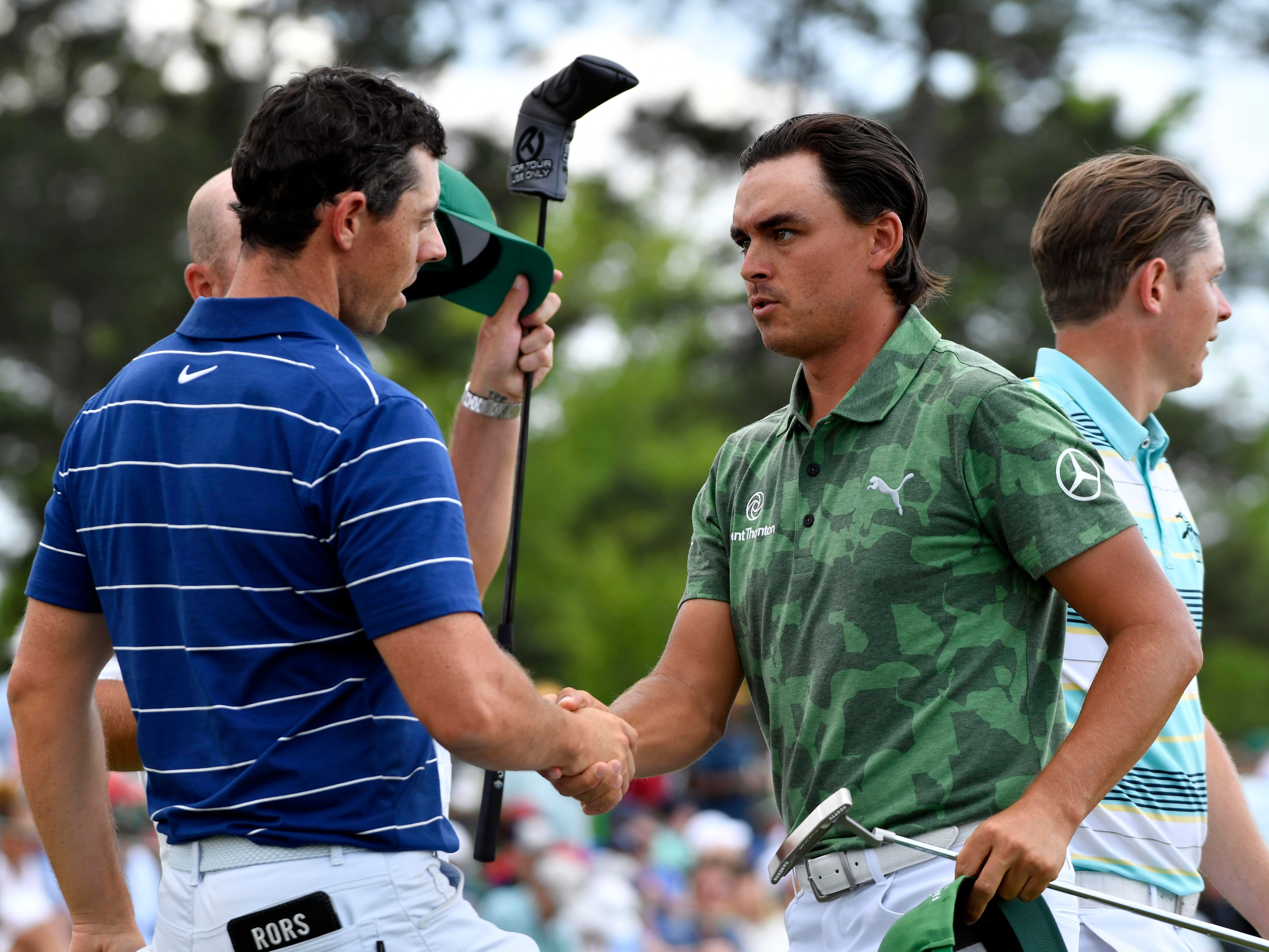 Apr 11, 2019; Augusta, GA, USA; Rickie Fowler (right) and Rory McIlroy (left) shake hands on the 18th green during the first round of The Masters golf tournament at Augusta National Golf Club.