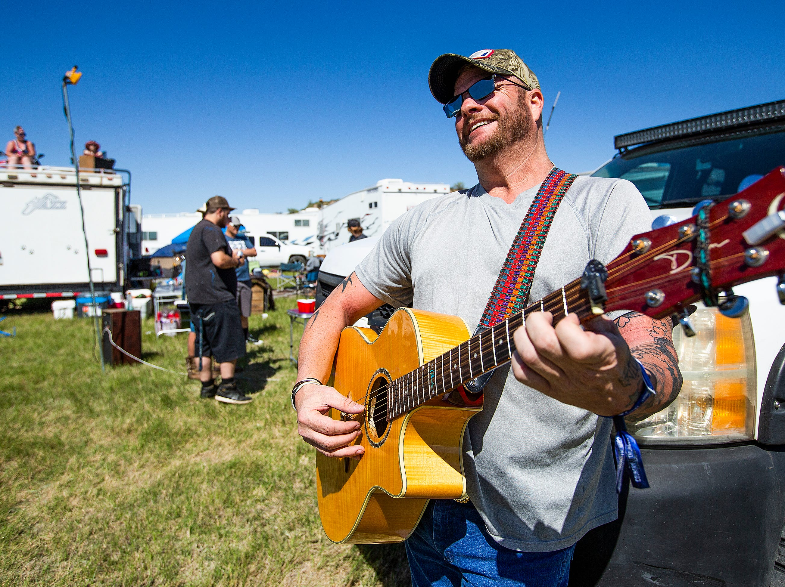 "Chade Woodard, 41, of Payson, plays his guitar and sings ""Thunder Rolls"" by Garth Brooks in his camp at the Country Thunder Arizona 2019 music festiva April 11, 2019."