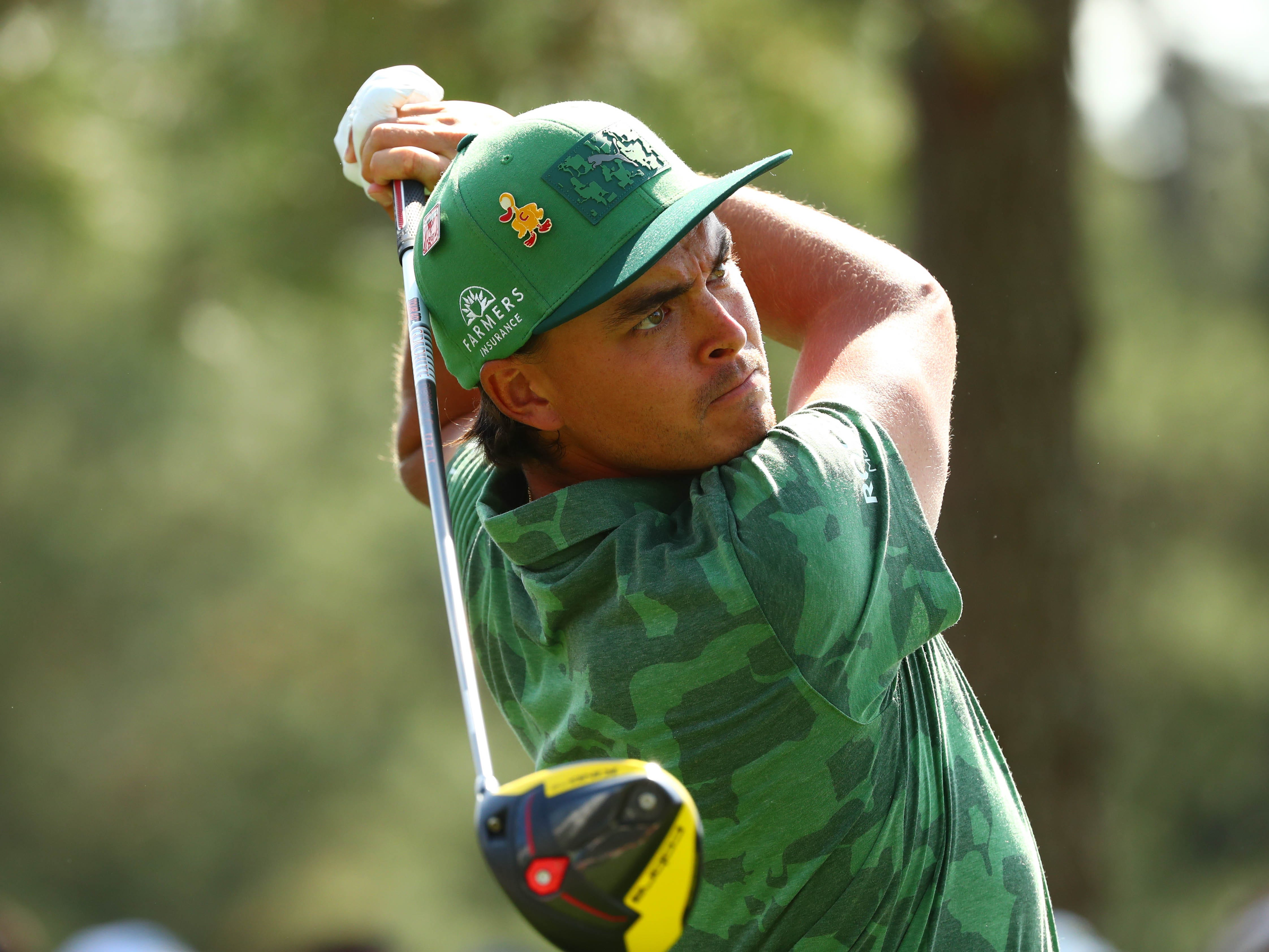 Apr 11, 2019; Augusta, GA, USA; Rickie Fowler hits his tee shot on the 18th hole during the first round of The Masters golf tournament at Augusta National Golf Club.
