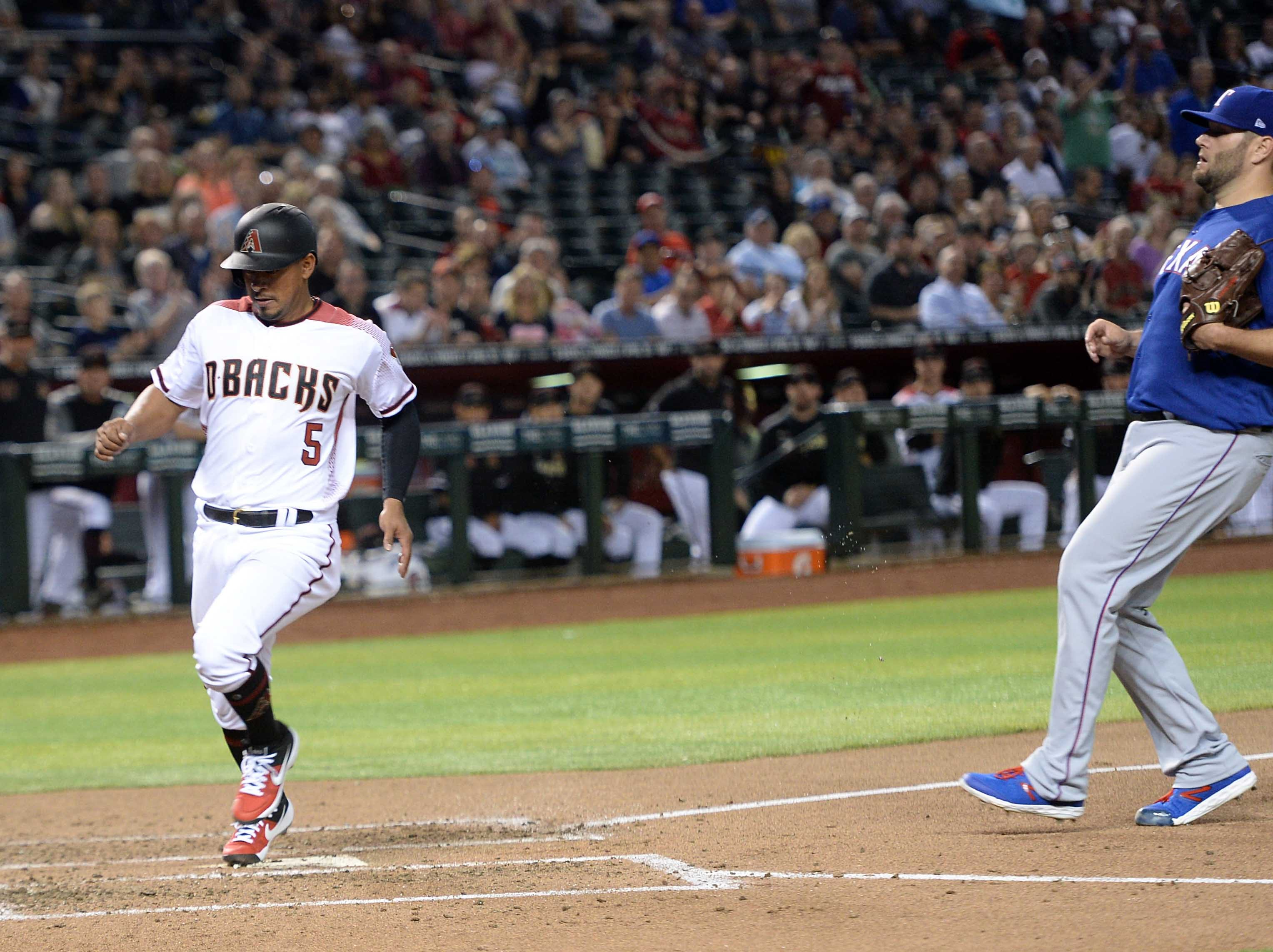 Apr 10, 2019; Phoenix, AZ, USA; Arizona Diamondbacks third baseman Eduardo Escobar (5) scores after a wild pitch by Texas Rangers starting pitcher Lance Lynn (35) during the third inning at Chase Field. Mandatory Credit: Joe Camporeale-USA TODAY Sports