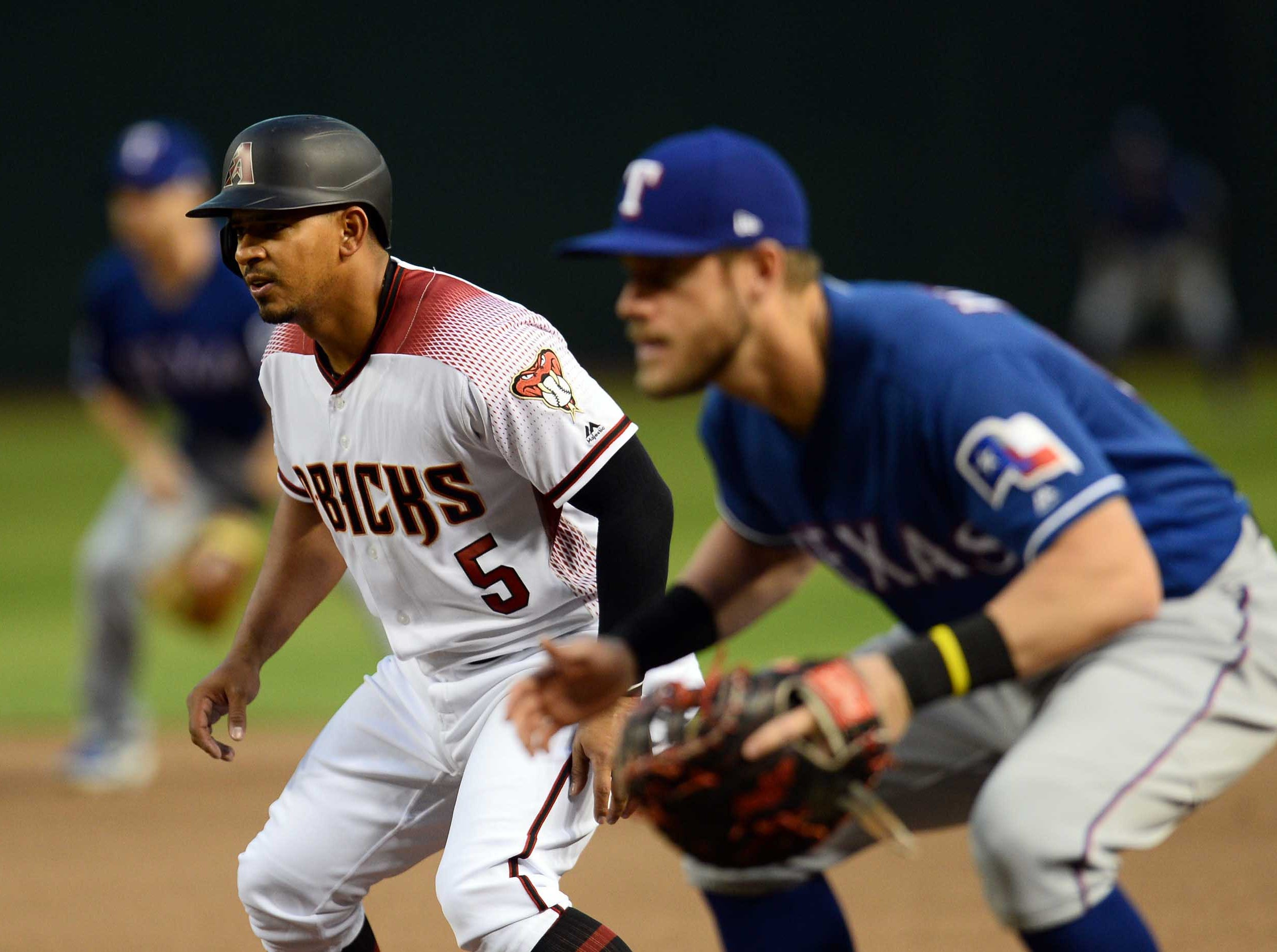Apr 10, 2019; Phoenix, AZ, USA; Arizona Diamondbacks third baseman Eduardo Escobar (5) leads off of first as as Texas Rangers first  baseman Patrick Wisdom covers the bag during the first inning at Chase Field. Mandatory Credit: Joe Camporeale-USA TODAY Sports