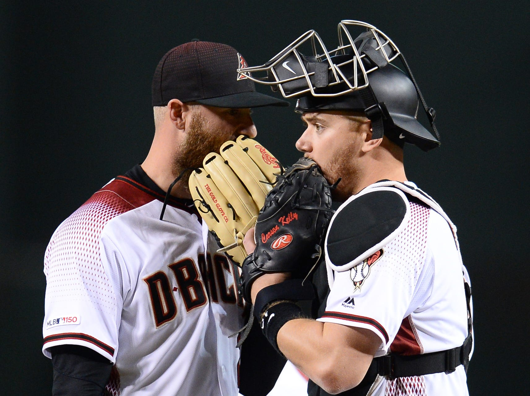Apr 10, 2019; Phoenix, AZ, USA; Arizona Diamondbacks relief pitcher Archie Bradley (25) talks with Arizona Diamondbacks catcher Carson Kelly (18) during the seventh inning against the Texas Rangers at Chase Field. Mandatory Credit: Joe Camporeale-USA TODAY Sports