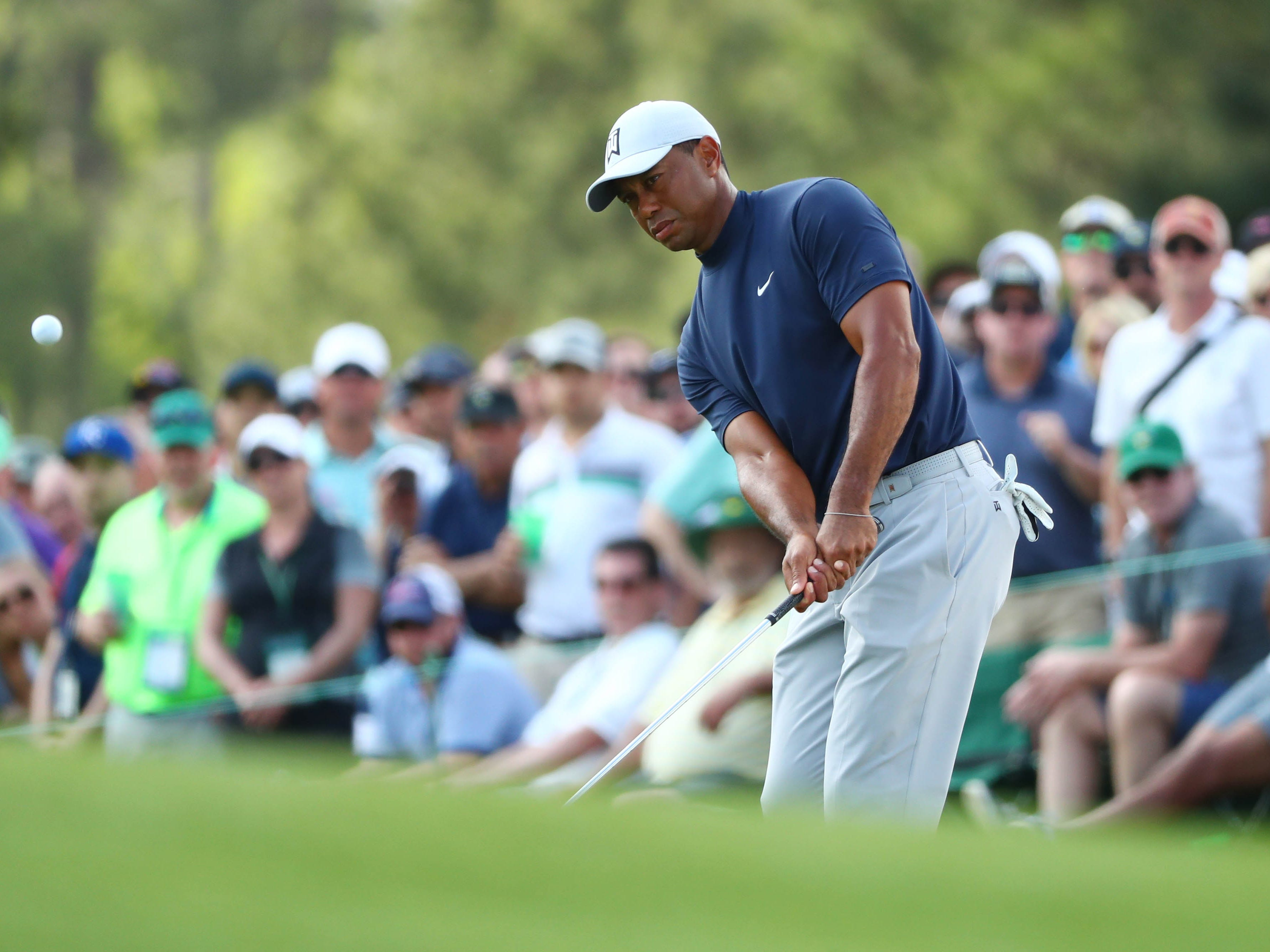 Apr 11, 2019; Augusta, GA, USA; Tiger Woods chips onto the 17th green during the first round of The Masters golf tournament at Augusta National Golf Club.