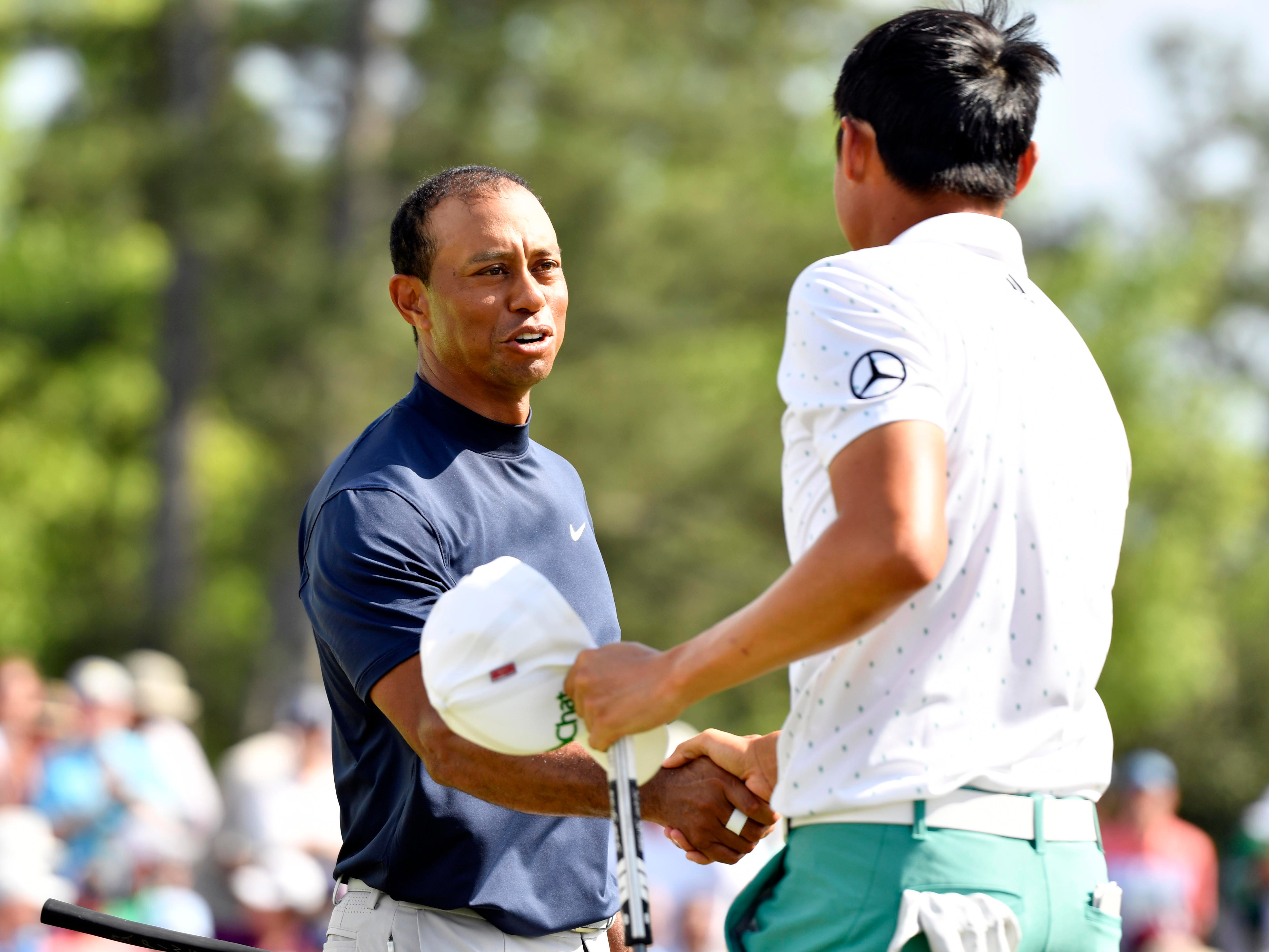 Apr 11, 2019; Augusta, GA, USA; Tiger Woods (left) shakes hands with Haotong Li (right) on the 18th green during the first round of The Masters golf tournament at Augusta National Golf Club.