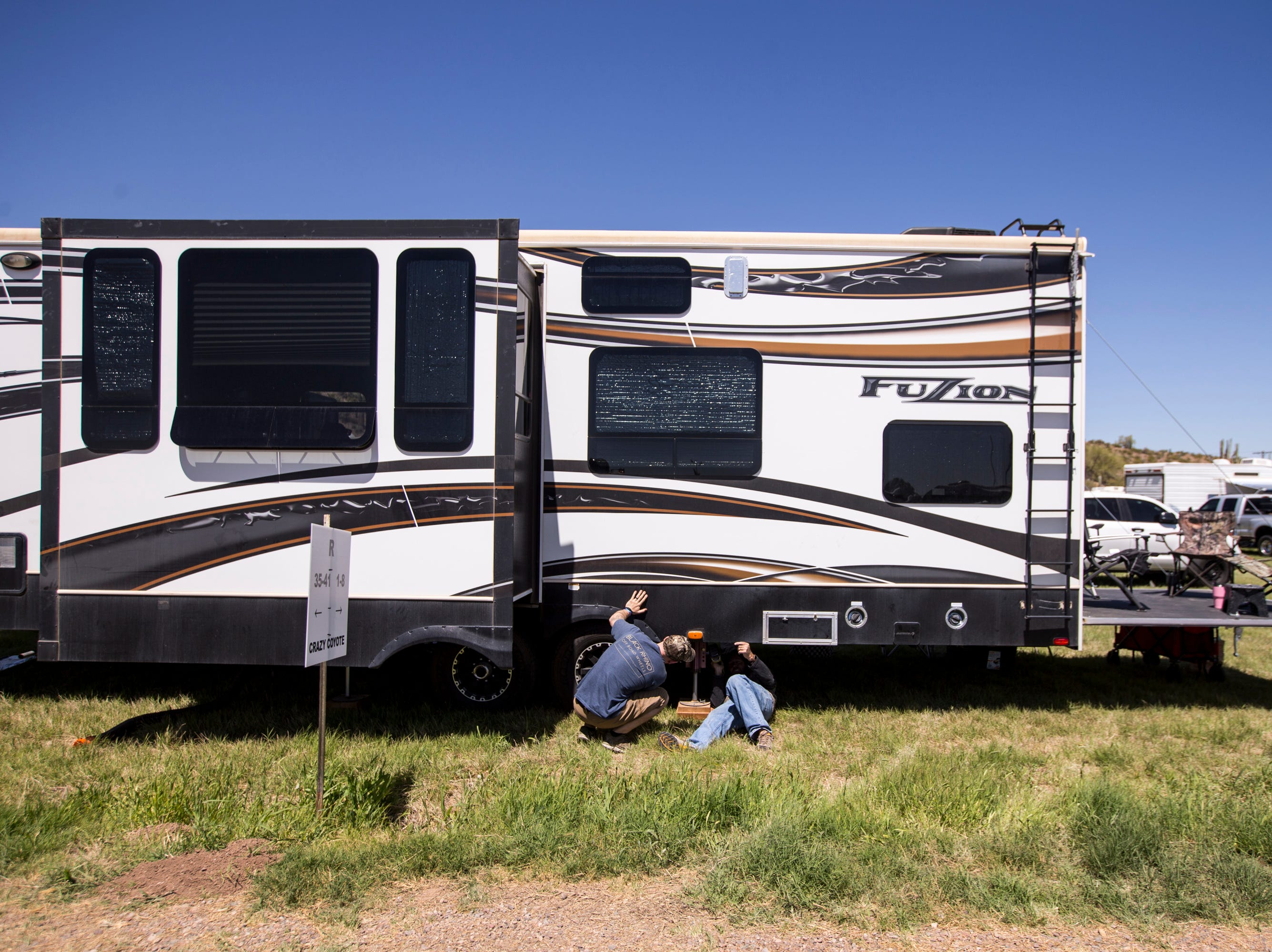 Mike Sonnenberg (left) and Kevin Blake work on their RV's electrical and drainage systems on April 11, 2019, during Day 1 of Country Thunder Arizona in Florence.