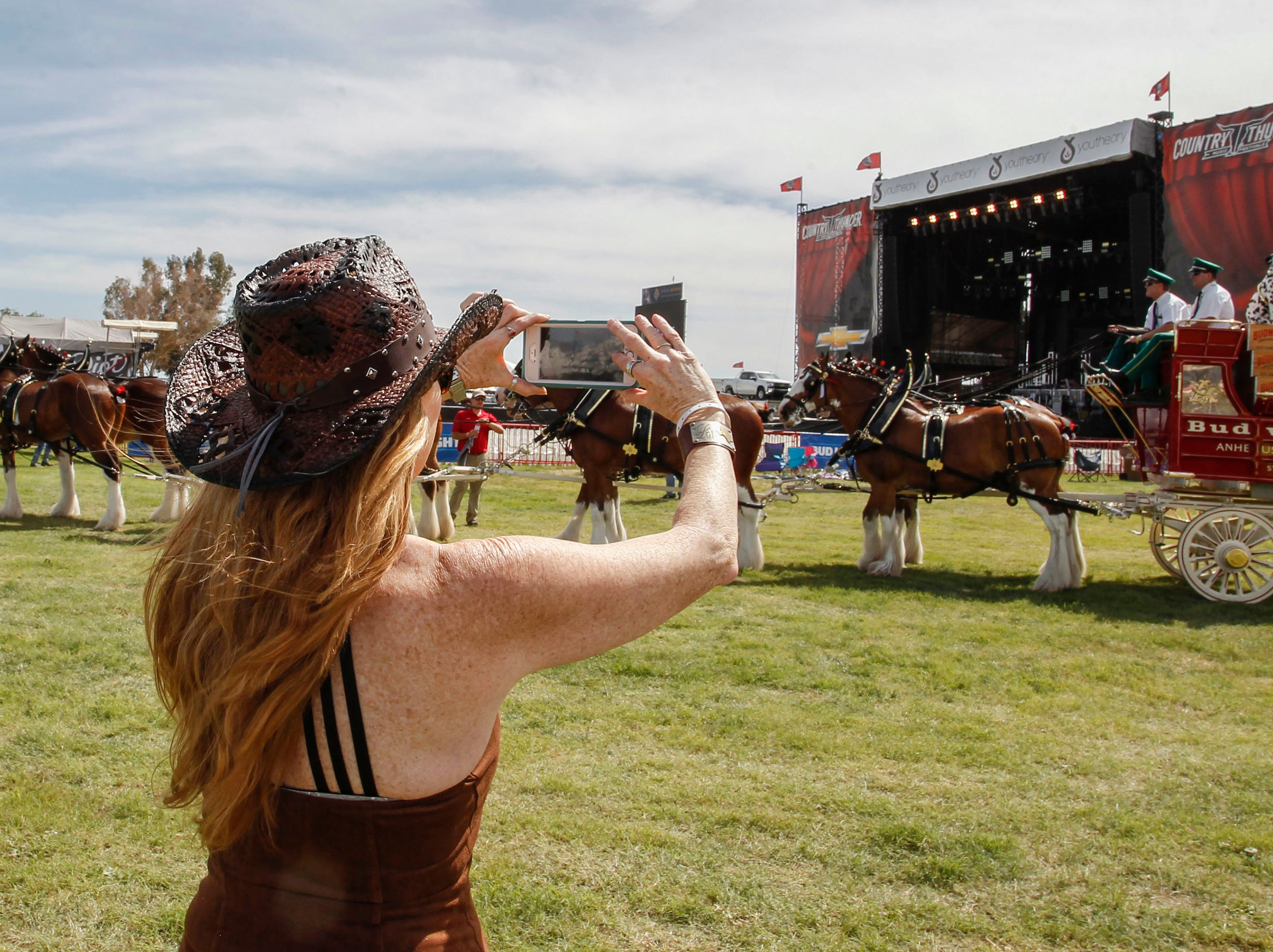Lavera Pettus of Texas takes a photo of the Budweiser Clydesdales as they strut their stuff during Country Thunder Arizona on April 11, 2019, in Florence.