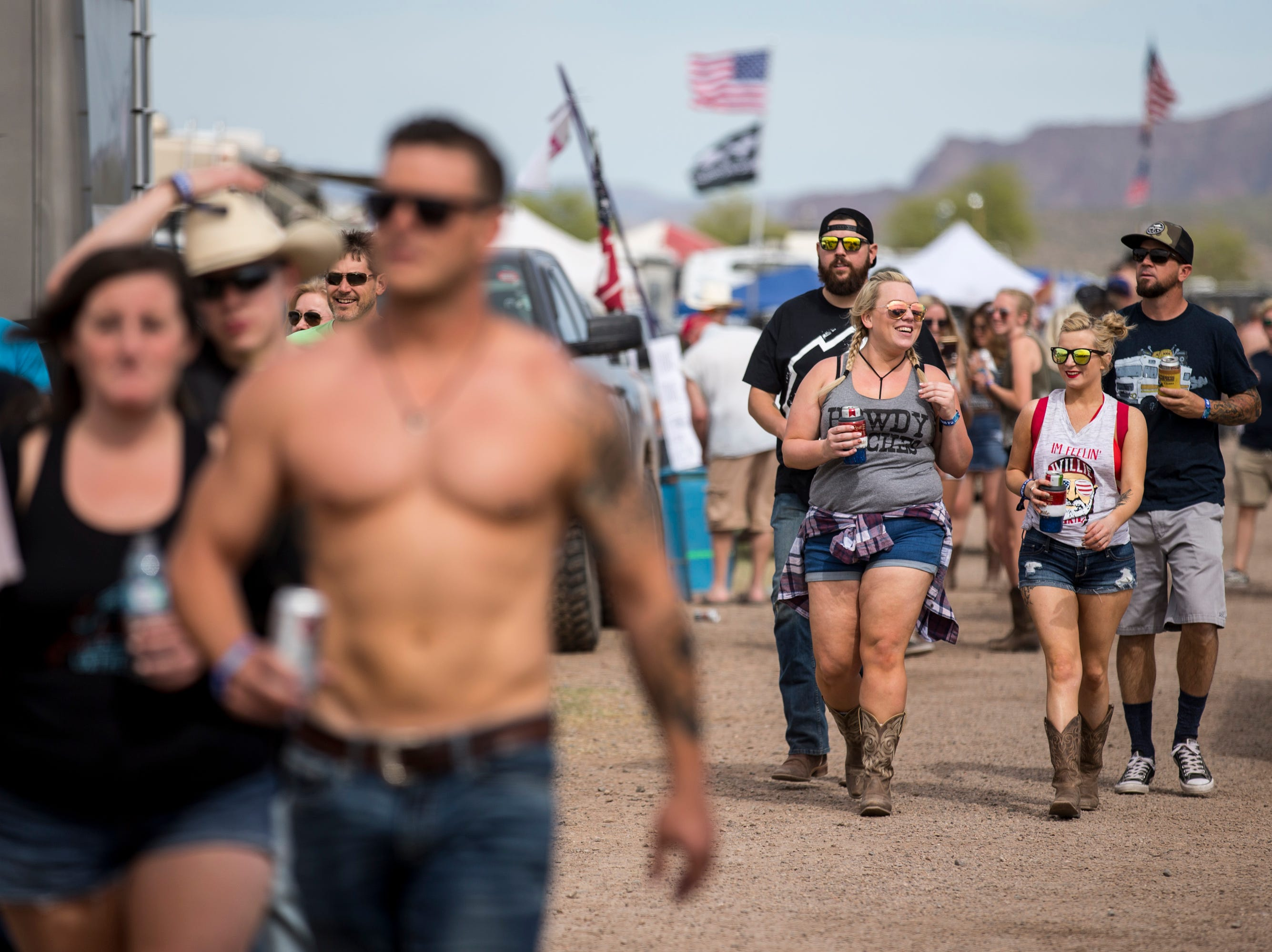 Festival-goers walk through the Crazy Coyote campsite on April 11, 2019, during Day 1 of Country Thunder Arizona in Florence.
