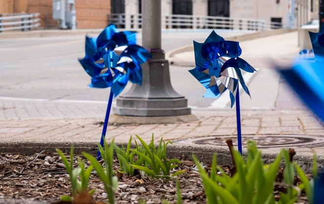 Blue pinwheels handed out by the St. Clair County Child Abuse/Neglect Council decorate the sidewalks along Huron Avenue Thursday, April 11, 2019 in Port Huron. The pinwheels, in addition to blue ribbons that were placed throughout downtown, are to raise awareness for Child Abuse Prevention Month.