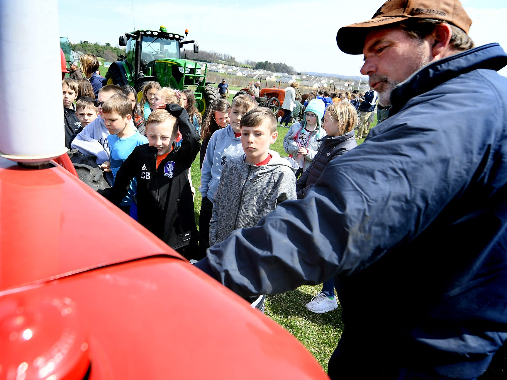 Carey Waugh of Shrewsbury Township answers a question for Spring Grove Elementary School fourth graders Landon Baker, left, and Jordan Eisenhart about the 1947 Farmall tractor he was showing during the district's 6th Annual Rollin' Tractor Show Thursday, April 11, 2019. The show is presented by the Future Farmers Club. Alumni and area residents brought farm equipment to display with the goal of acquainting students with the agriculture industry. The show, which included a parade of equipment, visited the intermediate and elementary schools. Bill Kalina photo