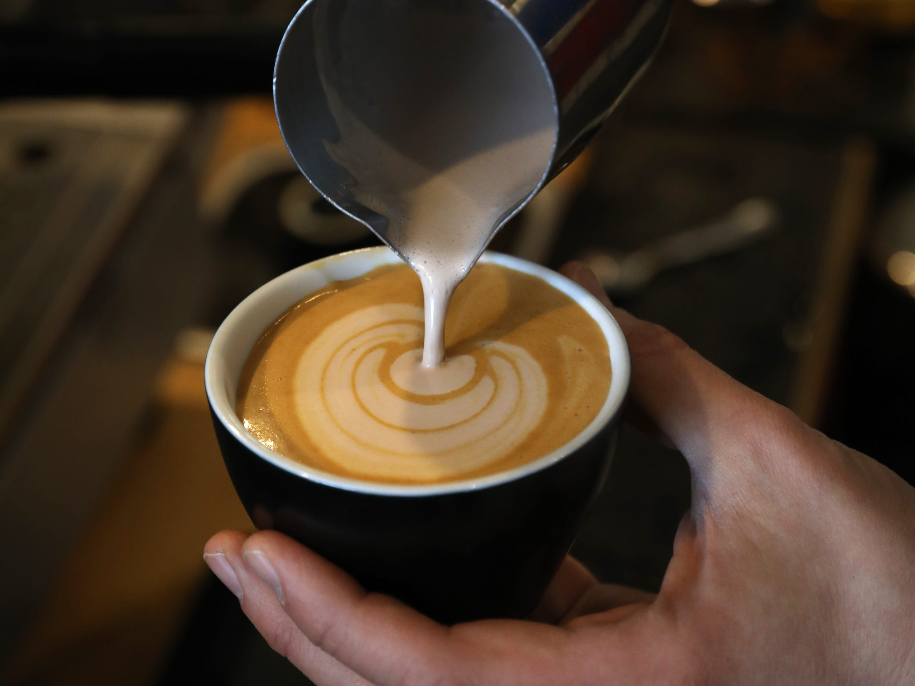 Adam Solomon, bar manager, puts the finishing pour on a chocolate milk cappuccino.