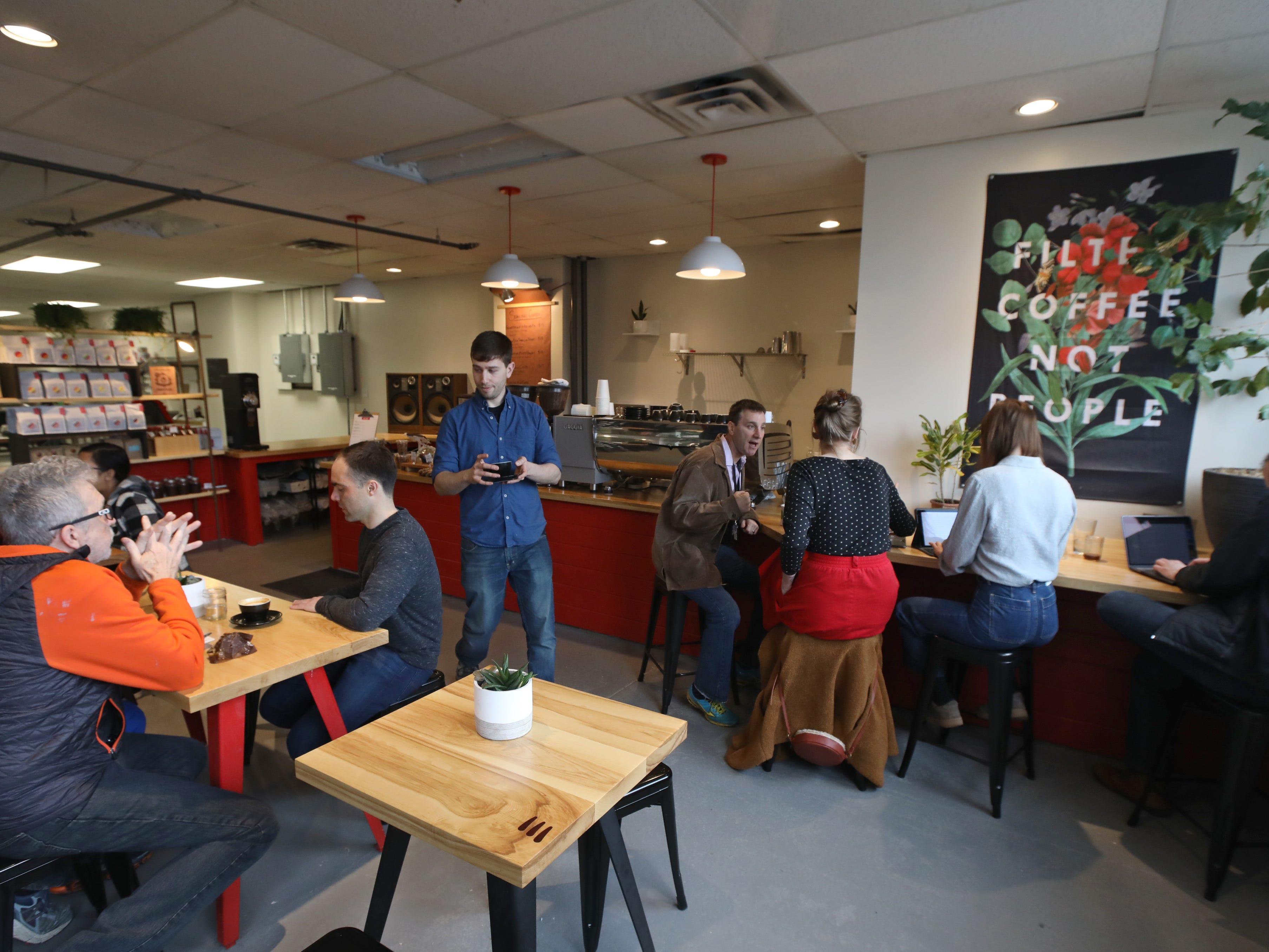 Adam Solomon, bar manager, center, serves up a freshly brewed mug of coffee inside the coffee bar.