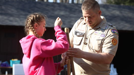 Tony Vogl, a visiting assistant scoutmaster, teaches Troop 425 how to make certain types of knots and lashing poles together.  Assisting him is Ellie Nonkes.