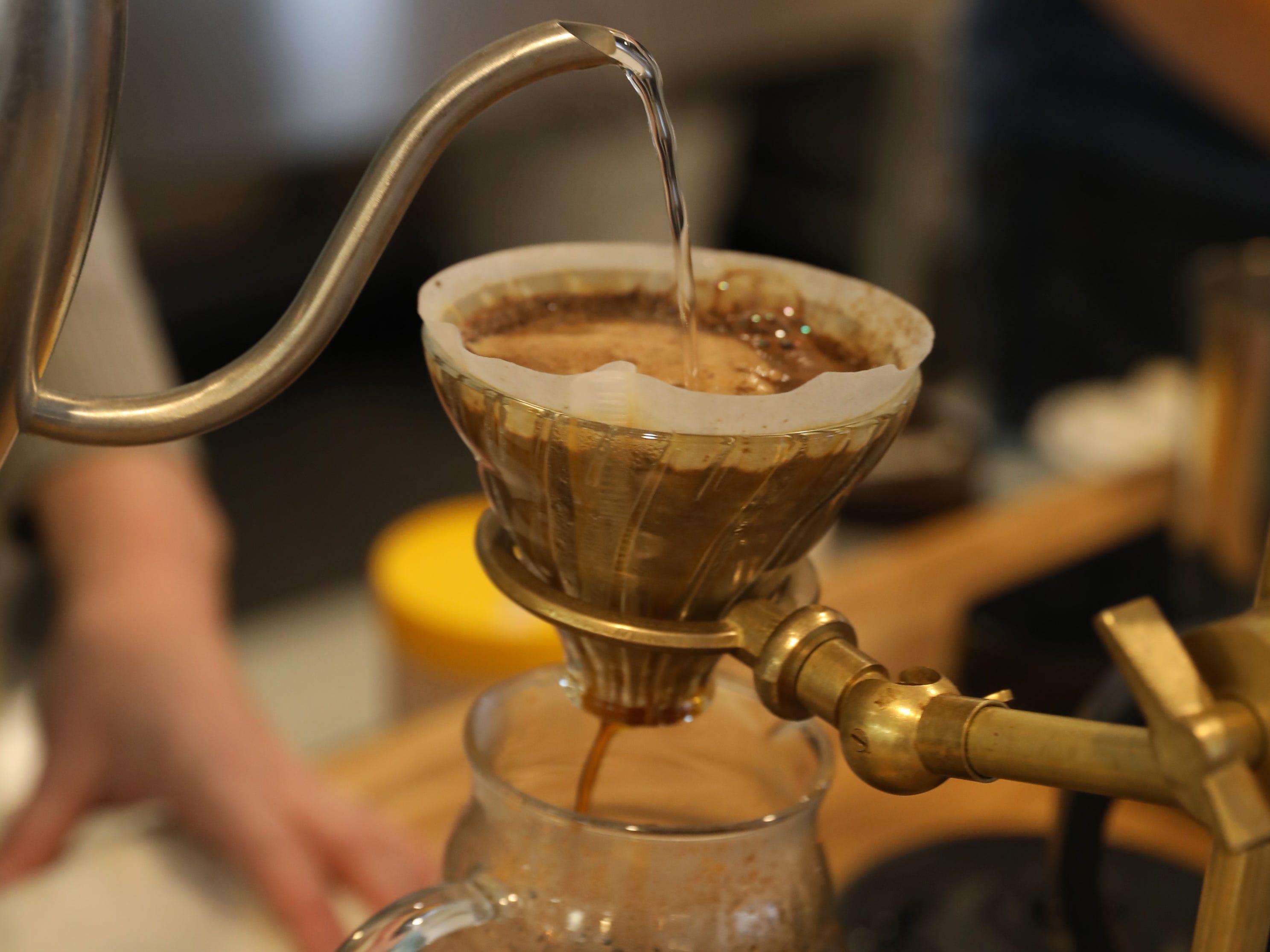 Dena Jones, partner, uses a Hario V60 brewing method as she prepares a order of Ethiopian coffee.