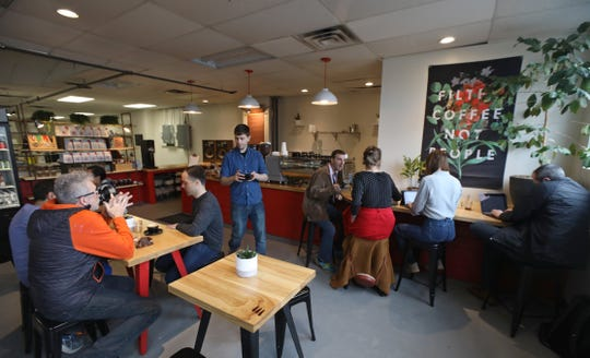 Adam Solomon, bar manager, center, serves up a freshly brewed mug of coffee at the new Joe Bean Coffee Roasters space at 565 Blossom Road Suite E1 in Rochester Thursday, April 11, 2019.