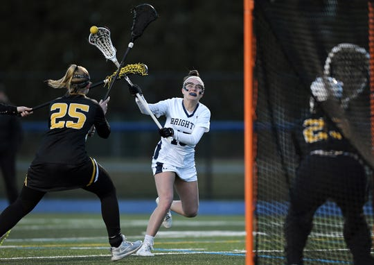 Brighton's Susan Lafountain, center, takes a shot on goal while defended by HF-L's Mackenzie Bushnell during a game at Brighton High School, Wednesday, April 10, 2019. Brighton beat Honeoye Falls-Lima 14-3.