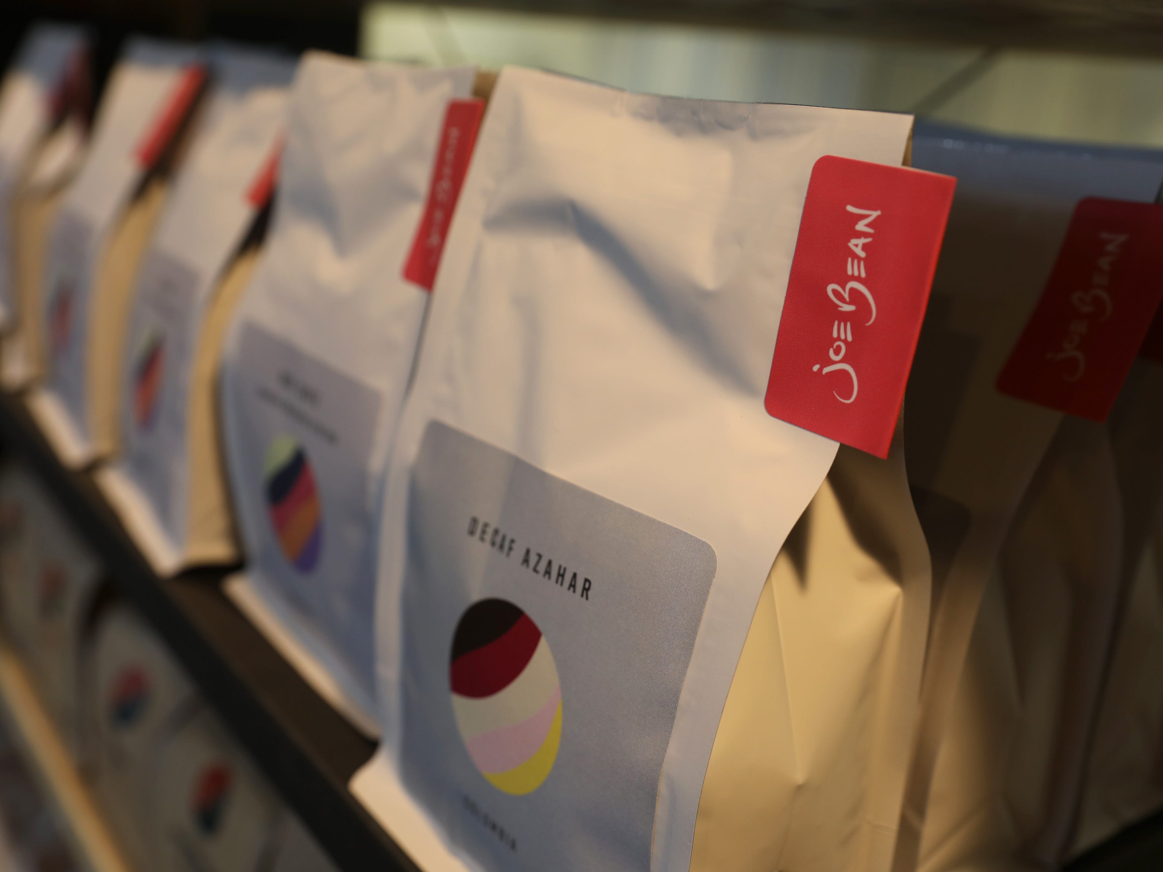 Bags of roasted coffee beans are offered for purchase.