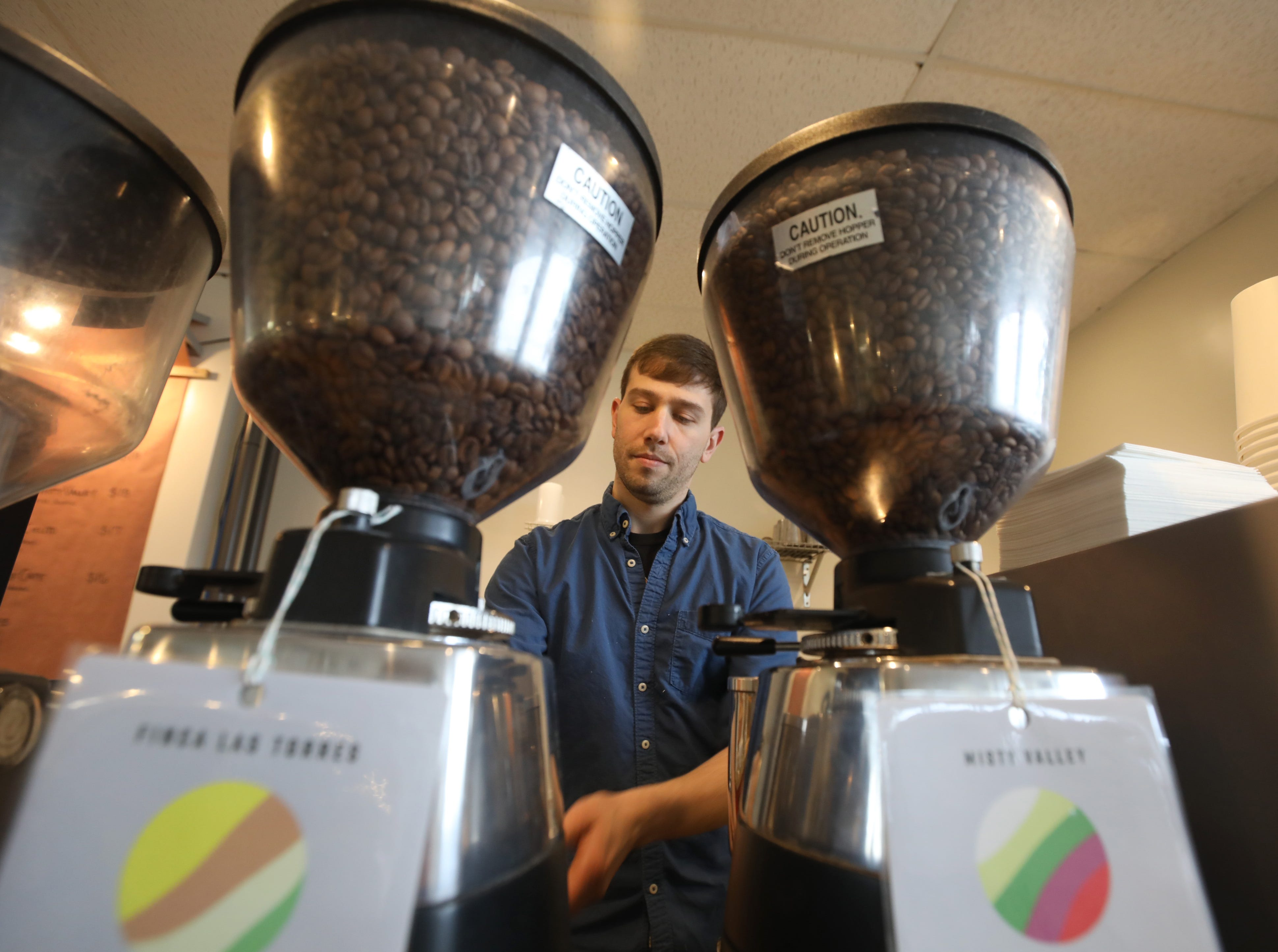 Adam Solomon, bar manager, grinds coffee beans as he fills an order at the new Joe Bean location.