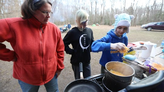 Cooks Lillian Graffrath,12, and Maddy Olek, 12, add more cheese after getting advice from their Scoutmaster Tiffany Drum. The troop makes their own dinner, they chose to make shepherd's pie. Troops ages 11-18 are single gender.
