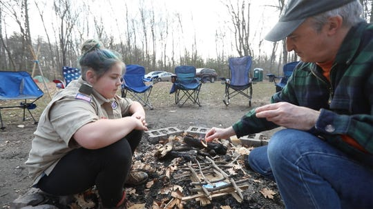 Dani Phillips,11, learns how to build a fire and the proper way to light it with a match from assistant scoutmaster Eric Drum. Troop 425 is a multi-grade, all-girl troop with Scouts BSA, a program of Boy Scouts of America.