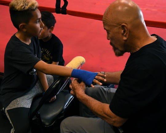 El entrenador Max García (derecha) cubre con cinta las manos de uno de los chicos locales que asiste a Team Villa Gym, antes de ponerse los guantes de boxeo.