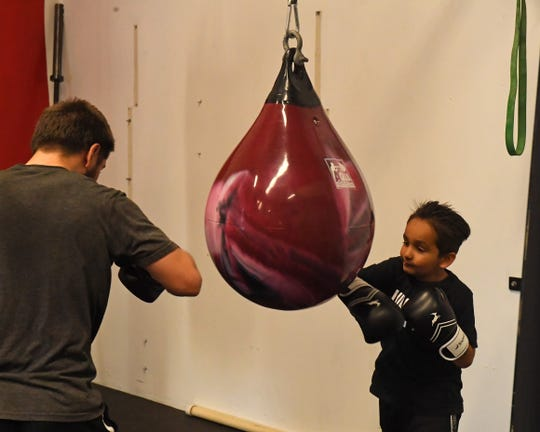 Ruben Villa IV (left) and one of the kids, Santana, train on the same heavy aqua bag at Team Villa Gym Tuesday afternoon.