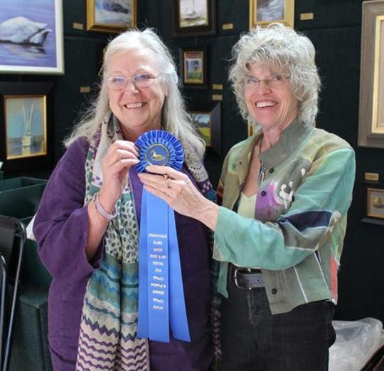 Nancy Richards West, right accepts the 2018 People's Choice Award at the 39th Annual Chincoteague Easter Decoy and Art Festival.