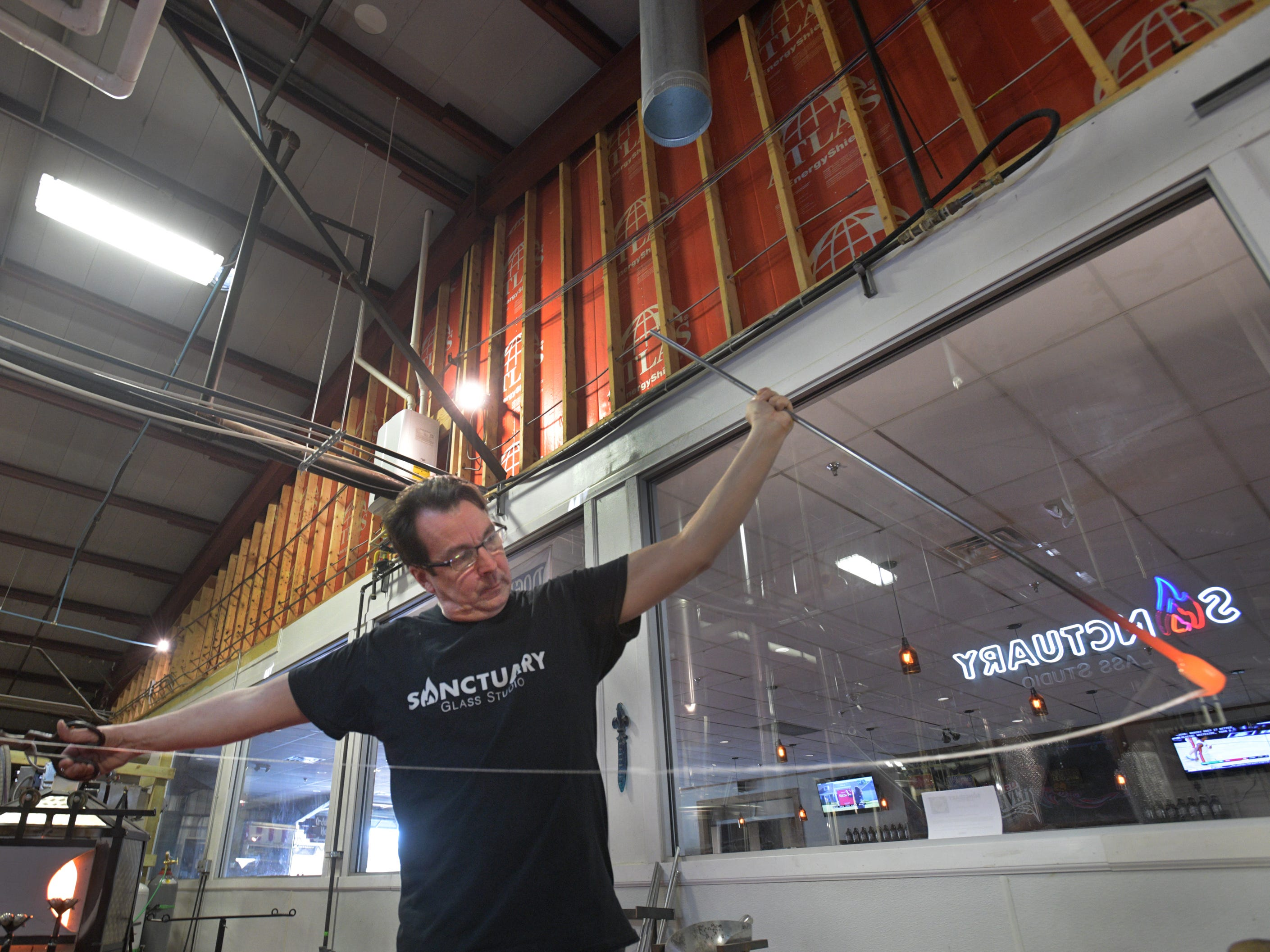 Sanctuary Glass Studio co-owner Eric Hess works glass into long strands.