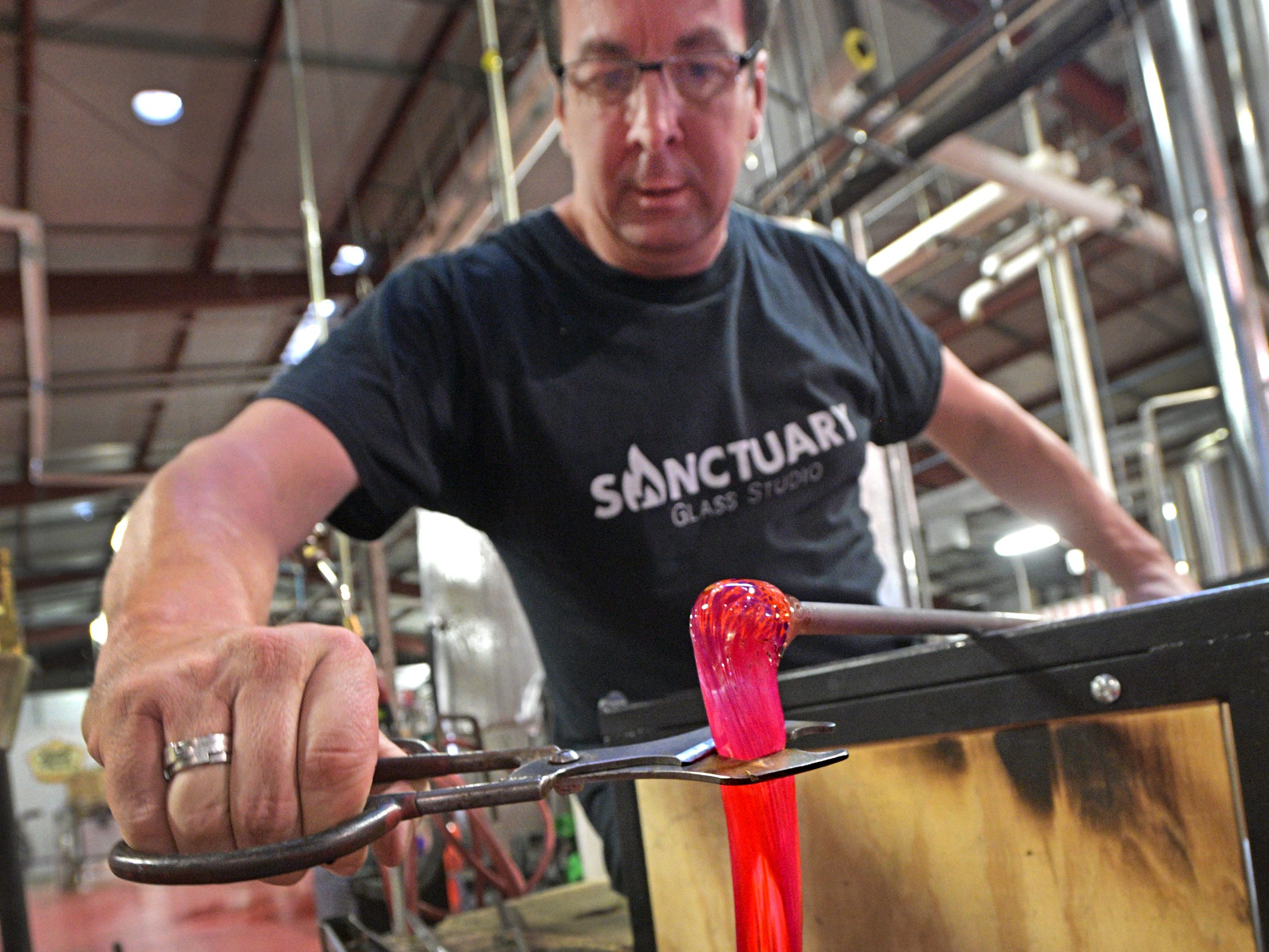 Sanctuary Glass Studio co-owner Eric Hess works glass into Art.