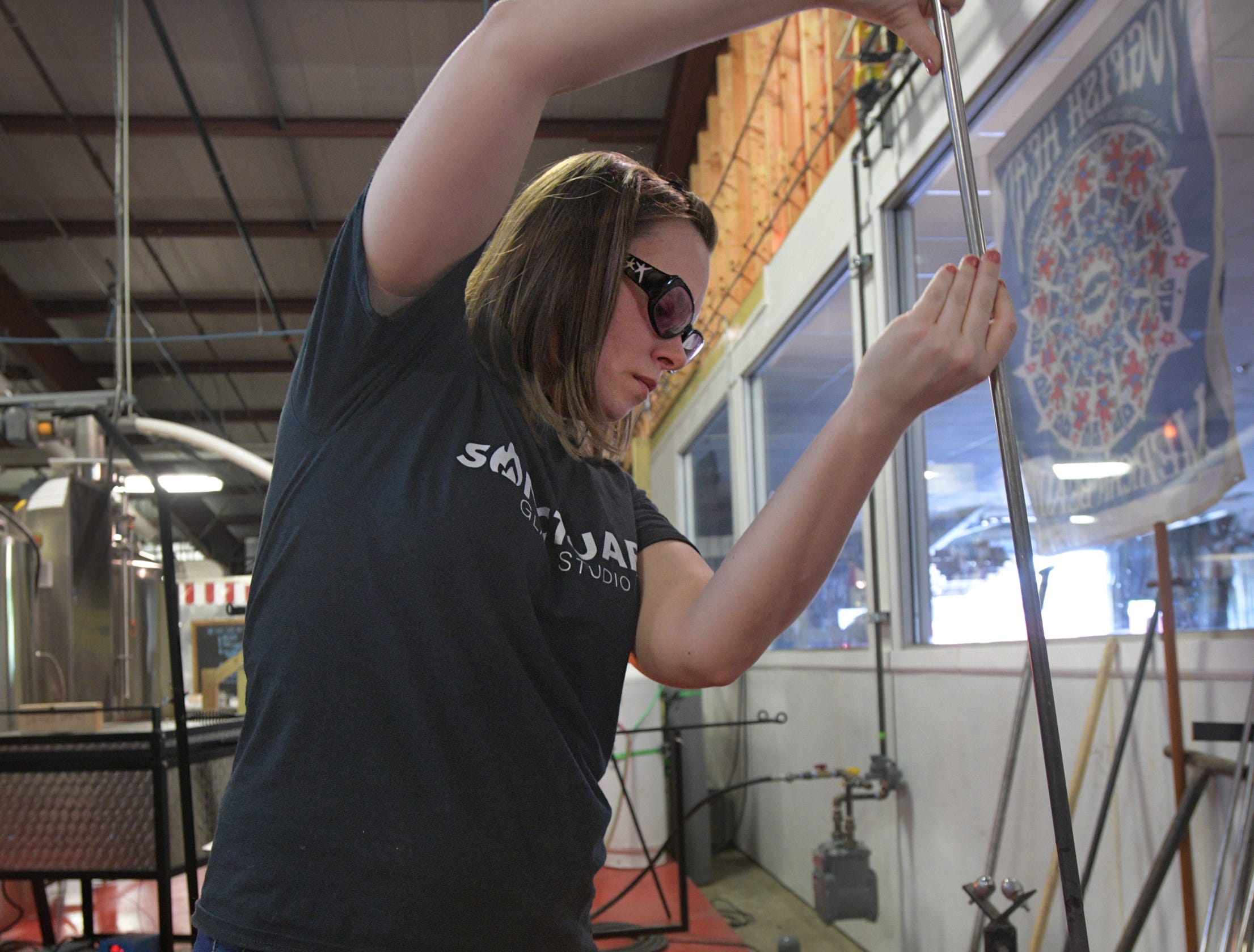 Sanctuary Glass Studio co-owner Michelle Pennington works with molten glass.